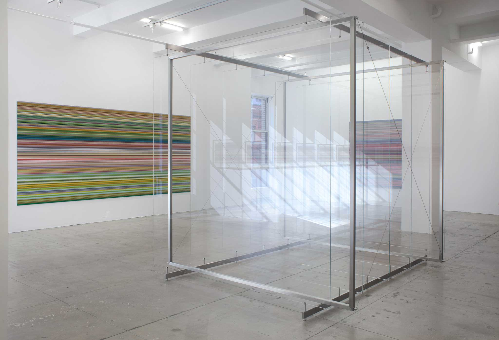 A floor-to-ceiling tall sculpture made of glass and steel in front of two paintings of red, yellow, green and black stripes.
