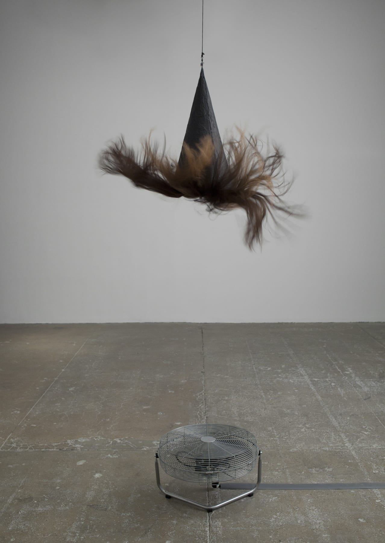A witch's hat with long brown hair hangs suspended above a fan.