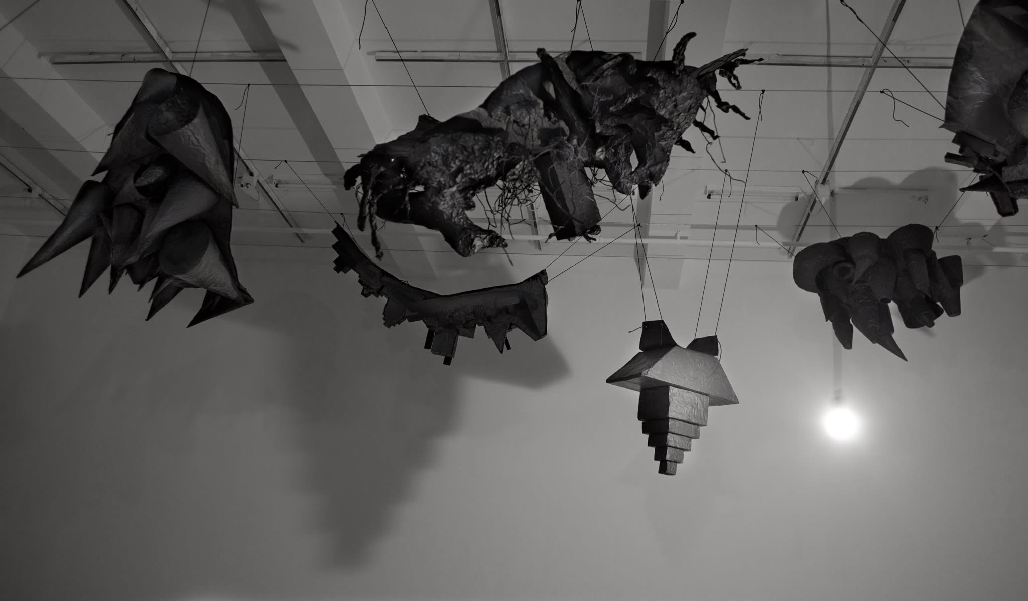 Five sculptures, four made of black fabric, hang suspended like bats in the air.