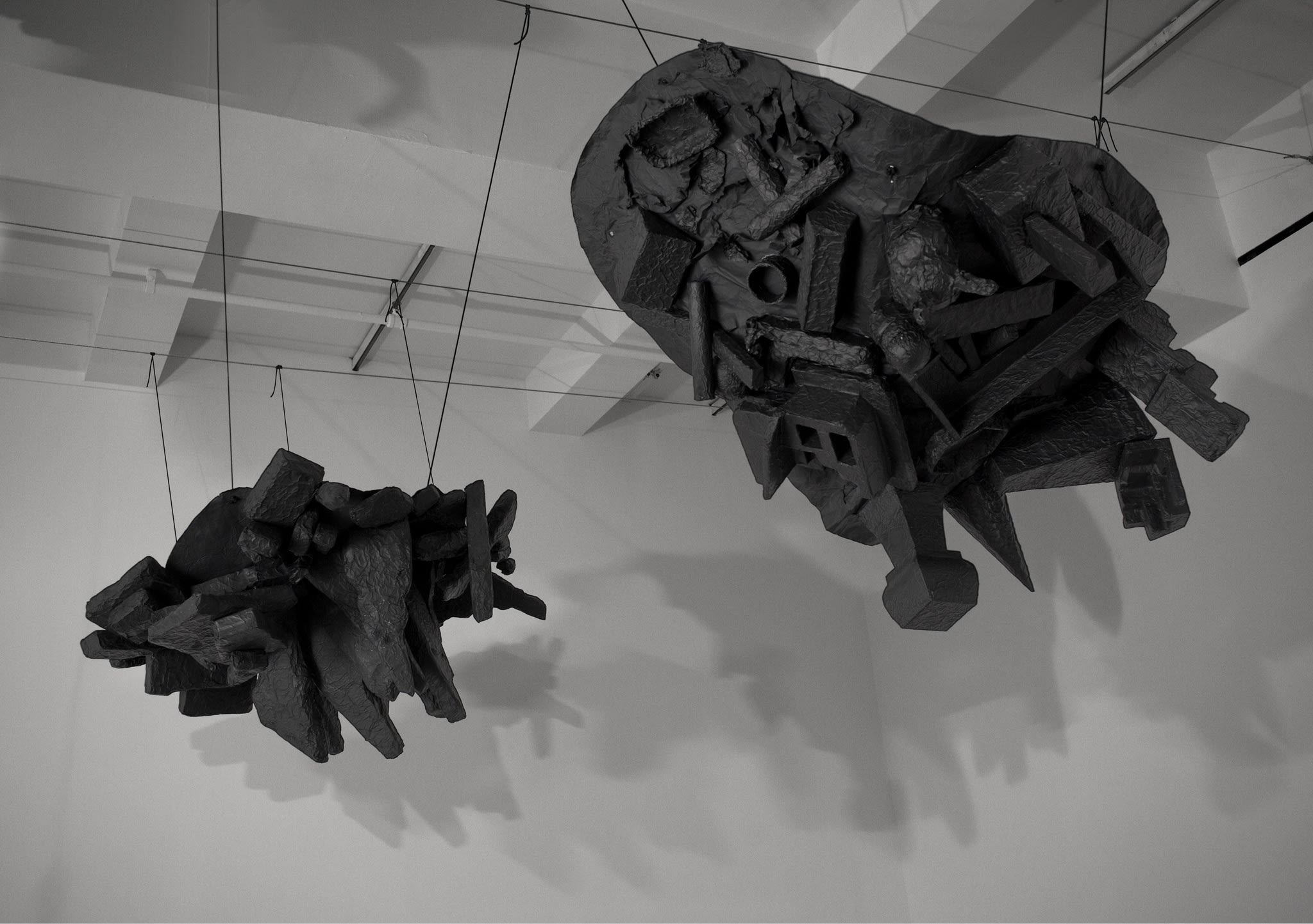 Two large black sculptures, one resembling a pile of stalactite and the other resembling a pile of detritus, hang from the ceiling.