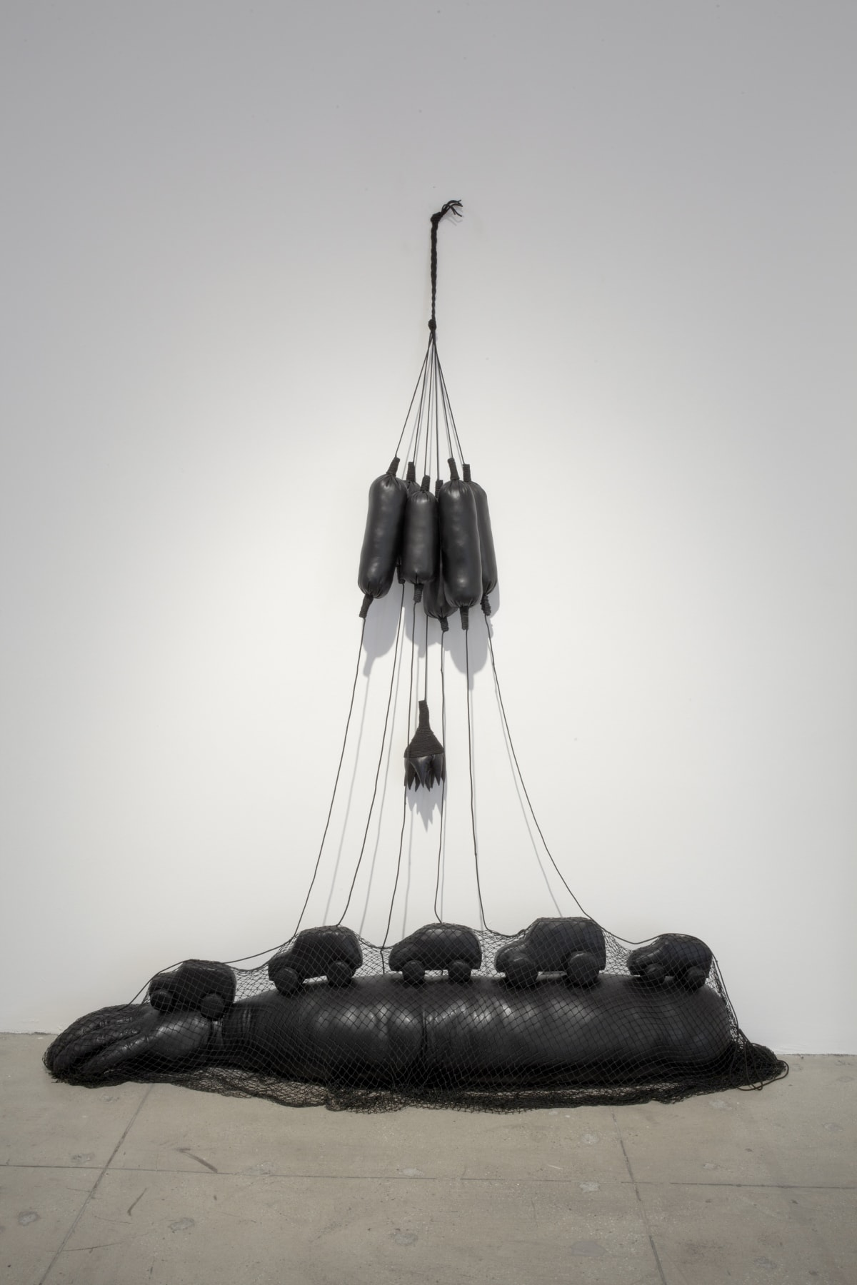 A black leather sculpture consisting of several small long balloons that is tied to a long leather arm on the floor that has cars driving on top of it.