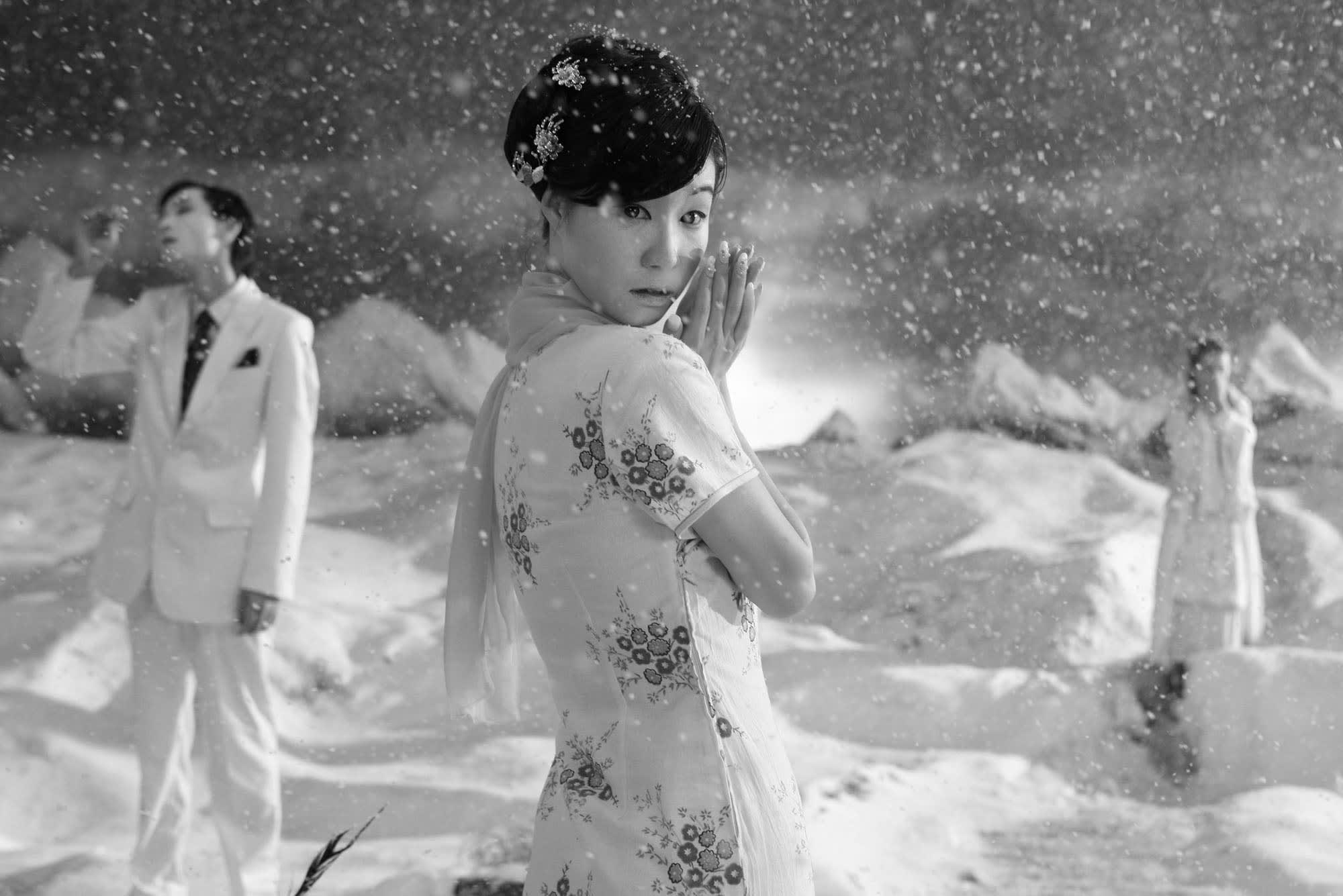 A black and white image of a woman in a floral dress standing in snowfall. A man in a suit stands to her left, while a figure is out of focus to the right.