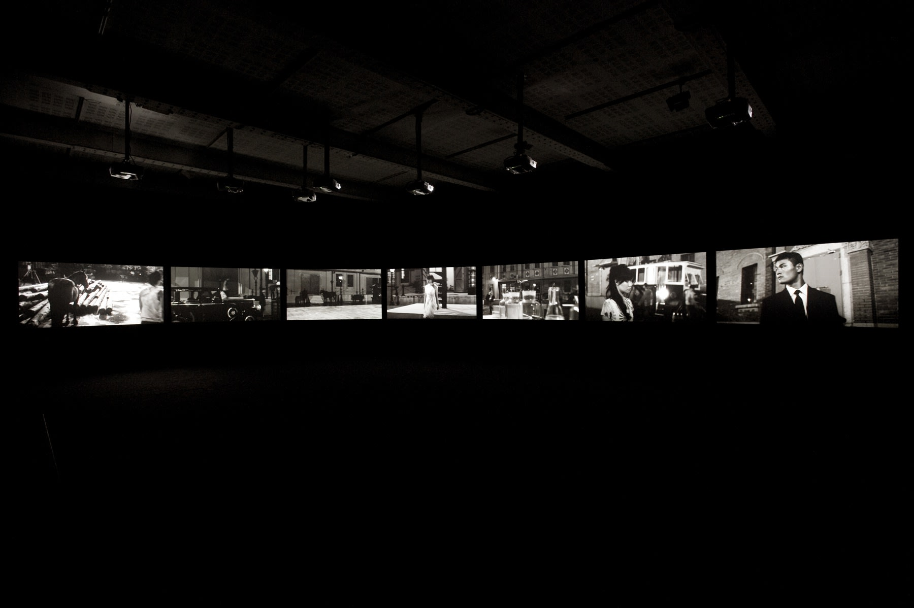 Seven projection screens arranged in a horizontal line in a large dark room. The black and white projections show city street scenes, a man and a woman.