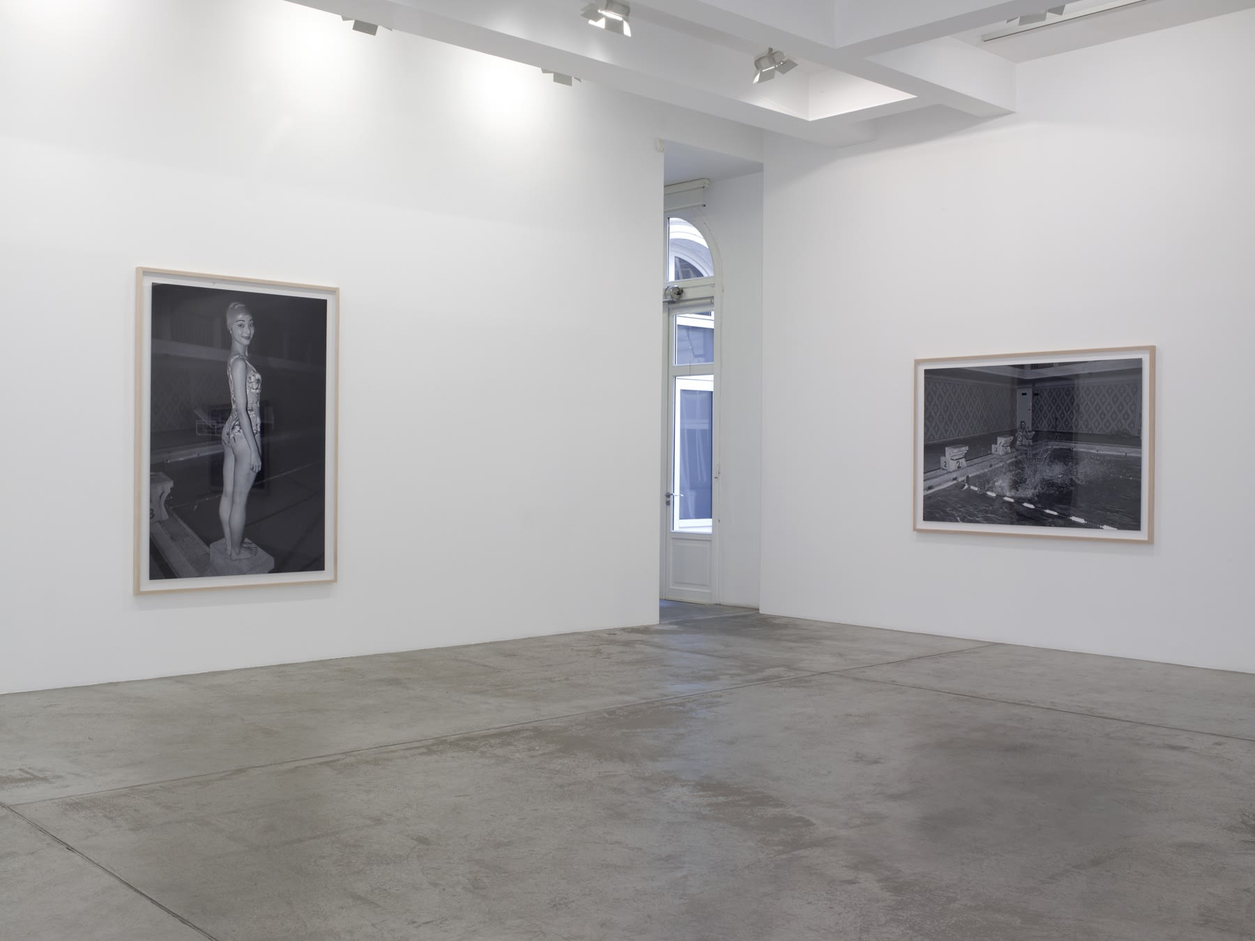 Two framed black and white photographs hanging in the corner of the room, one of a woman in a diving cap at an indoor pool, and the second of water splashing after a dive.