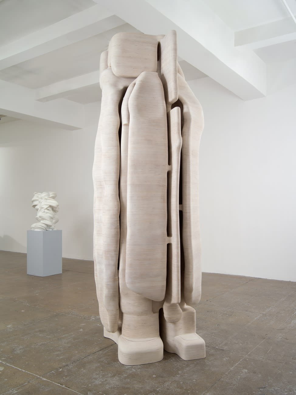 On the left sits a white abstract sculpture on a pedestal; central is a large, beige, vertical abstract sculpture.