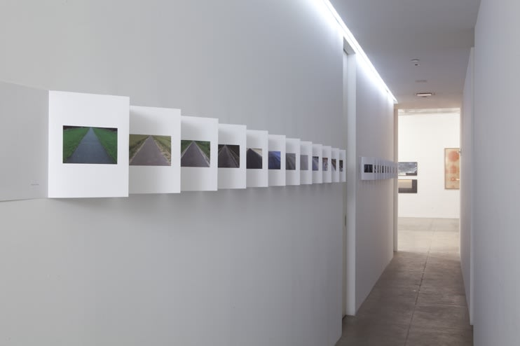 Multiple photographs line the left side of a hallway in a book-style format.