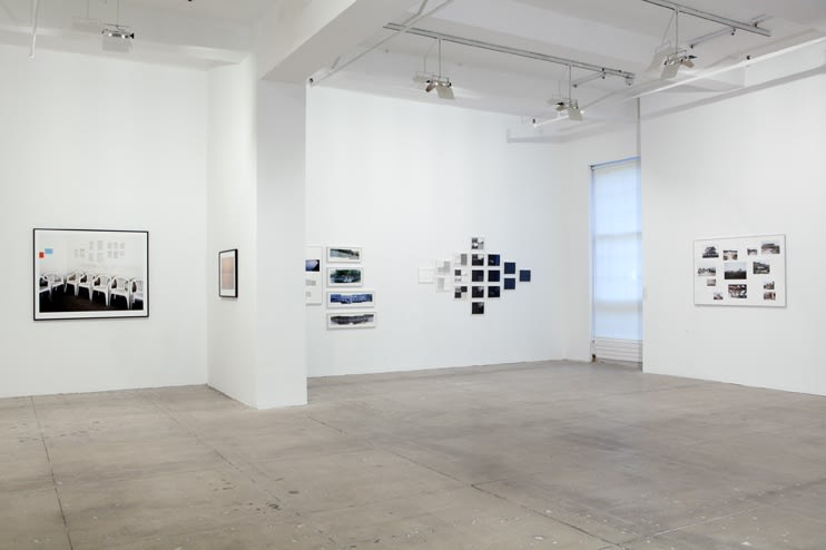 Multiple photographic works fill the walls of a large white room.