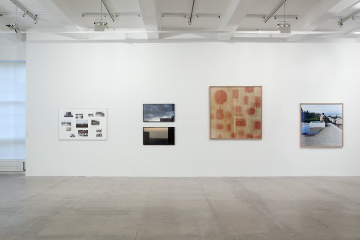 Four photographic works are displayed on a white wall.