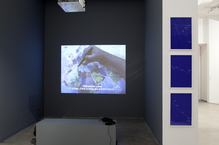 Three blue prints of a map hang alongside a projection of a hand drawing over a map.