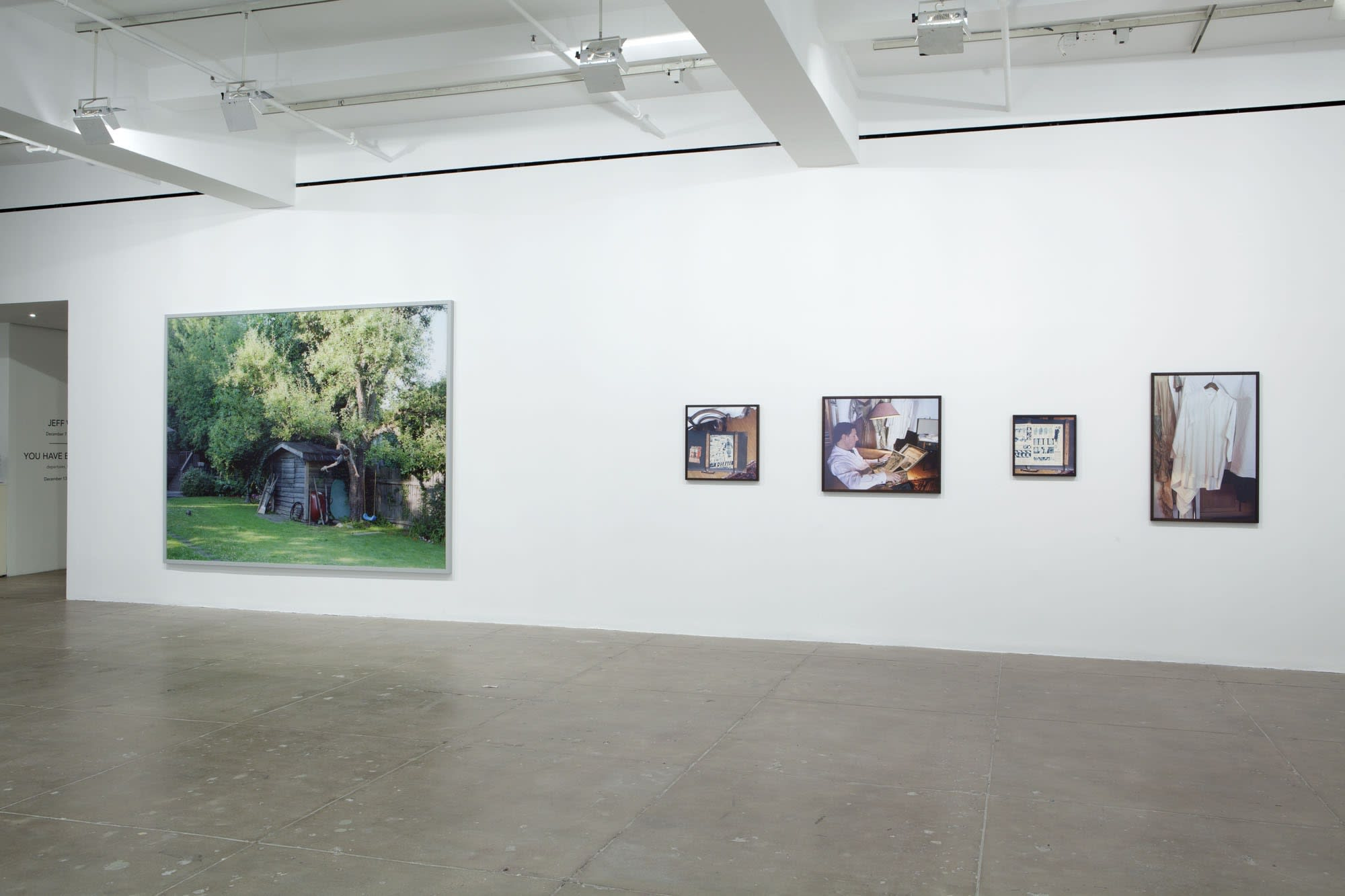 One large photograph of a treehouse hangs alongside four small images of clothes, a man reading and knick-knacks.