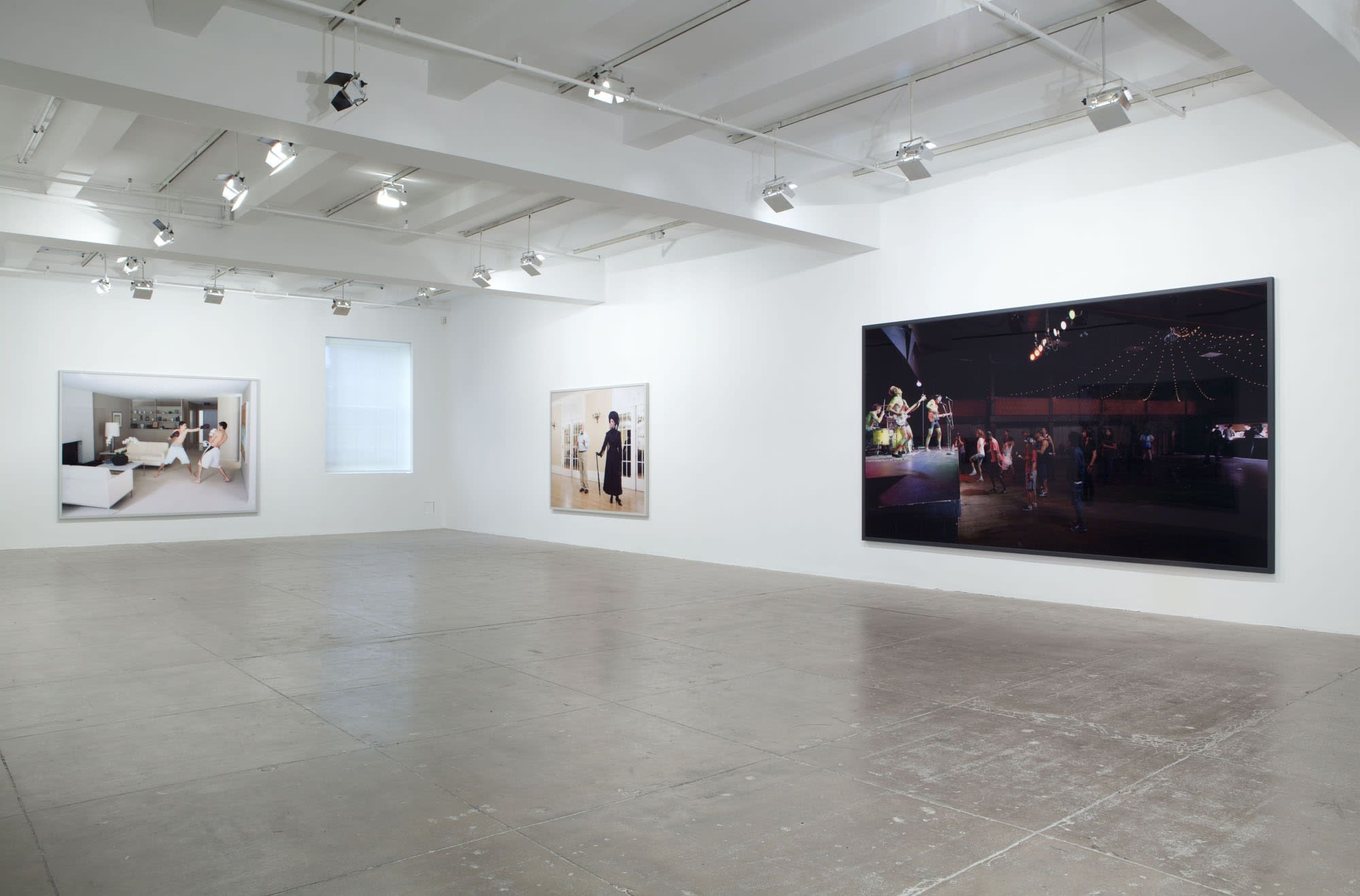 An image of two boys boxing, an image of an elegant woman dressed in black and an nighttime image of an outdoor concert are displayed in a white room.