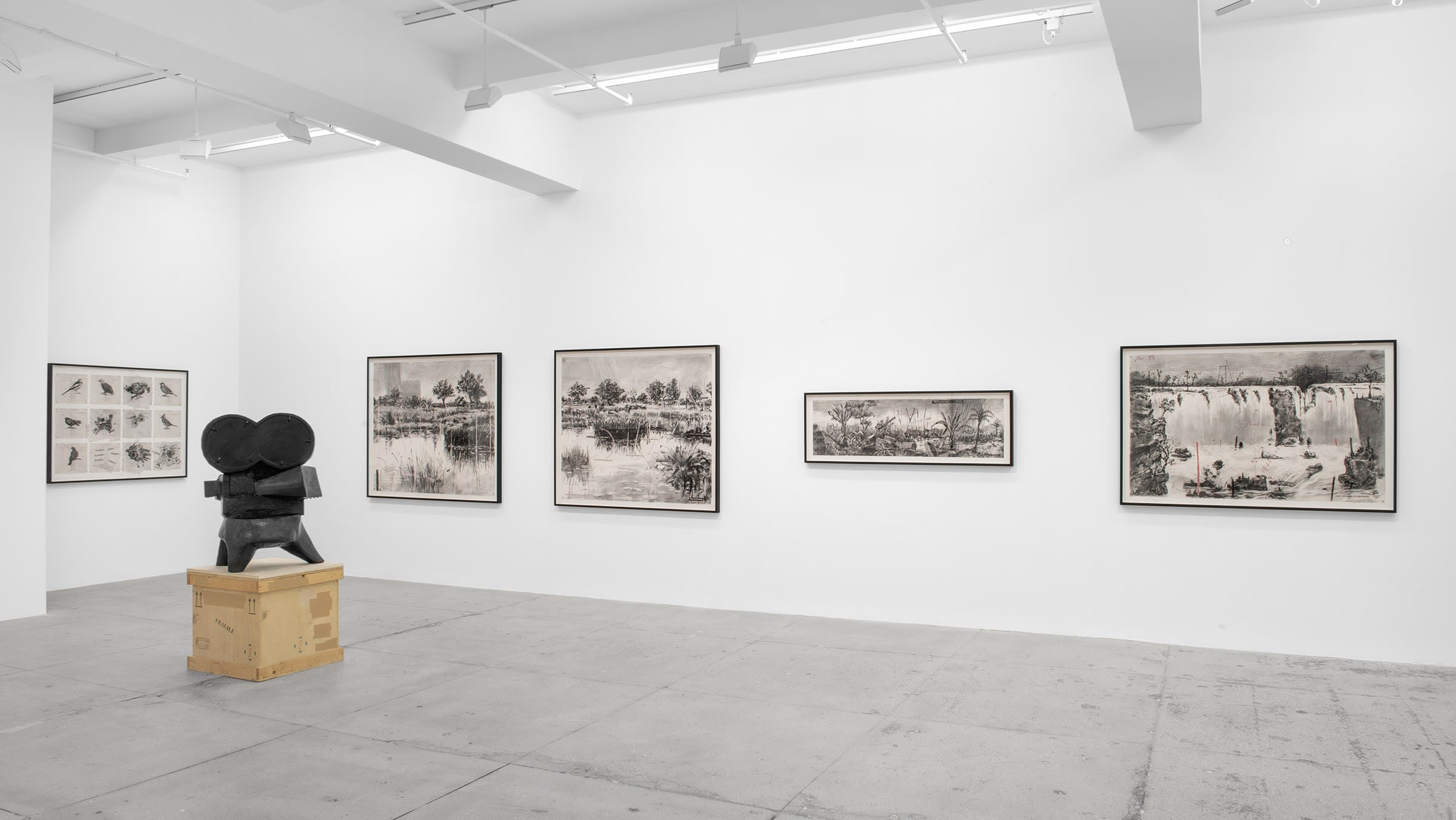 A copper sculpture of an old Hollywood camera stands in front of five graphite drawings of maps, plants and landscapes.