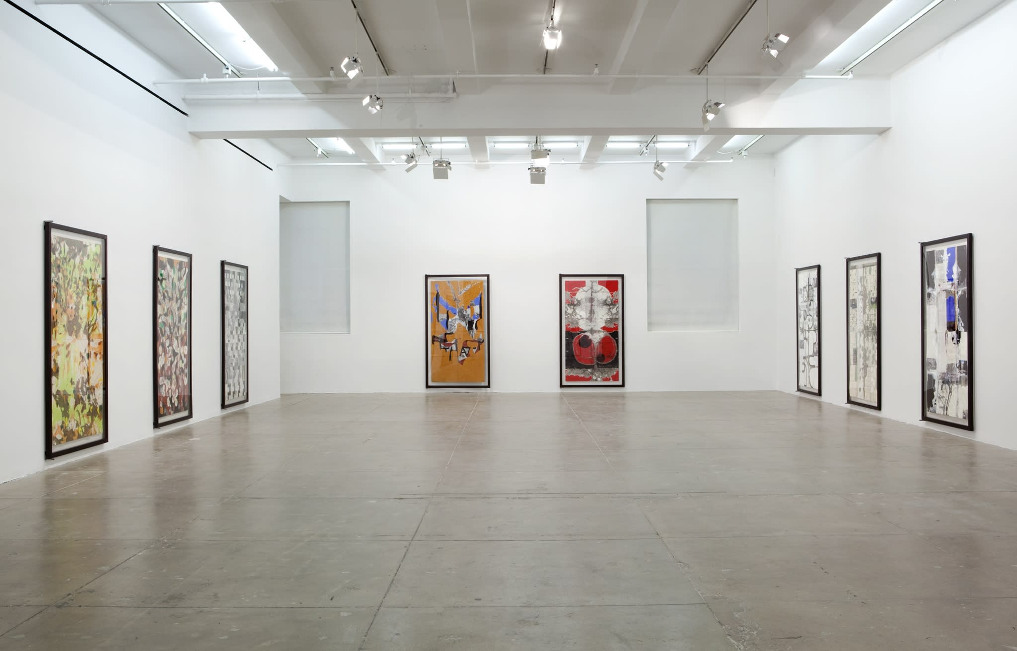 Eight large vertical abstract paintings fill the walls of a large white room.