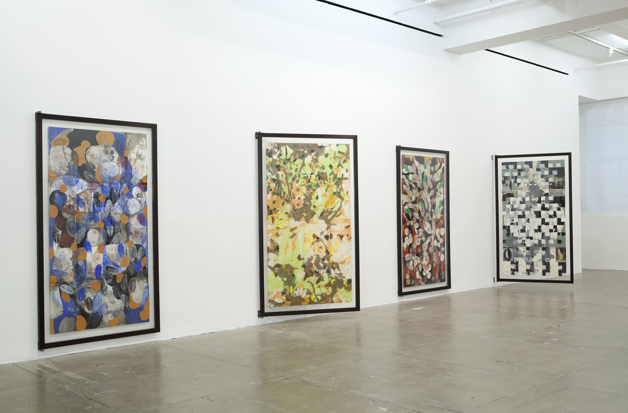Four large paintings of abstract shapes and various colors are displayed on hinges to view the front and back.