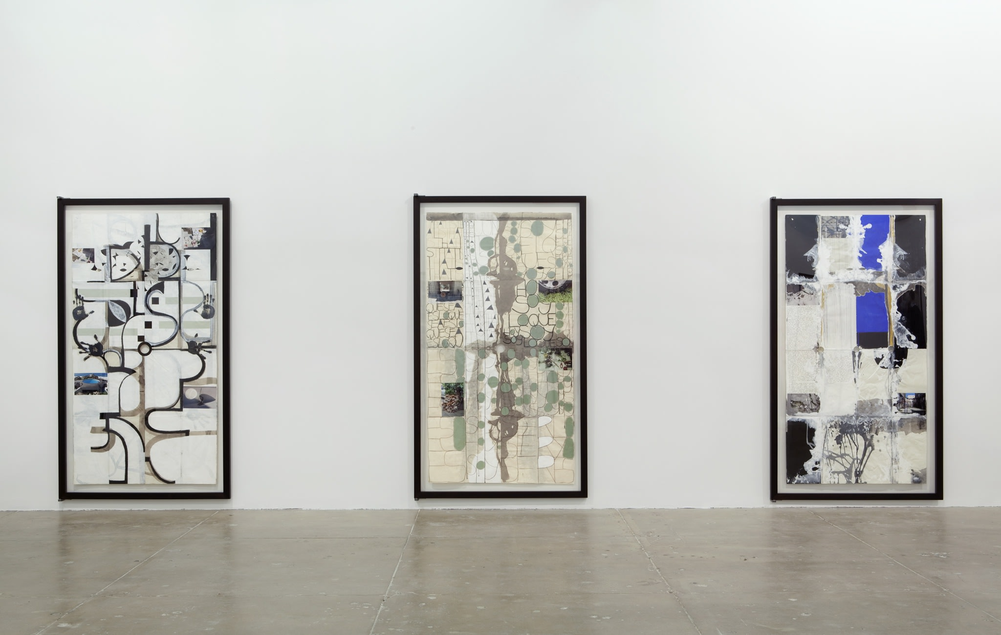 Three large vertical paintings of organic shapes and monochromatic colors hang on a white wall.
