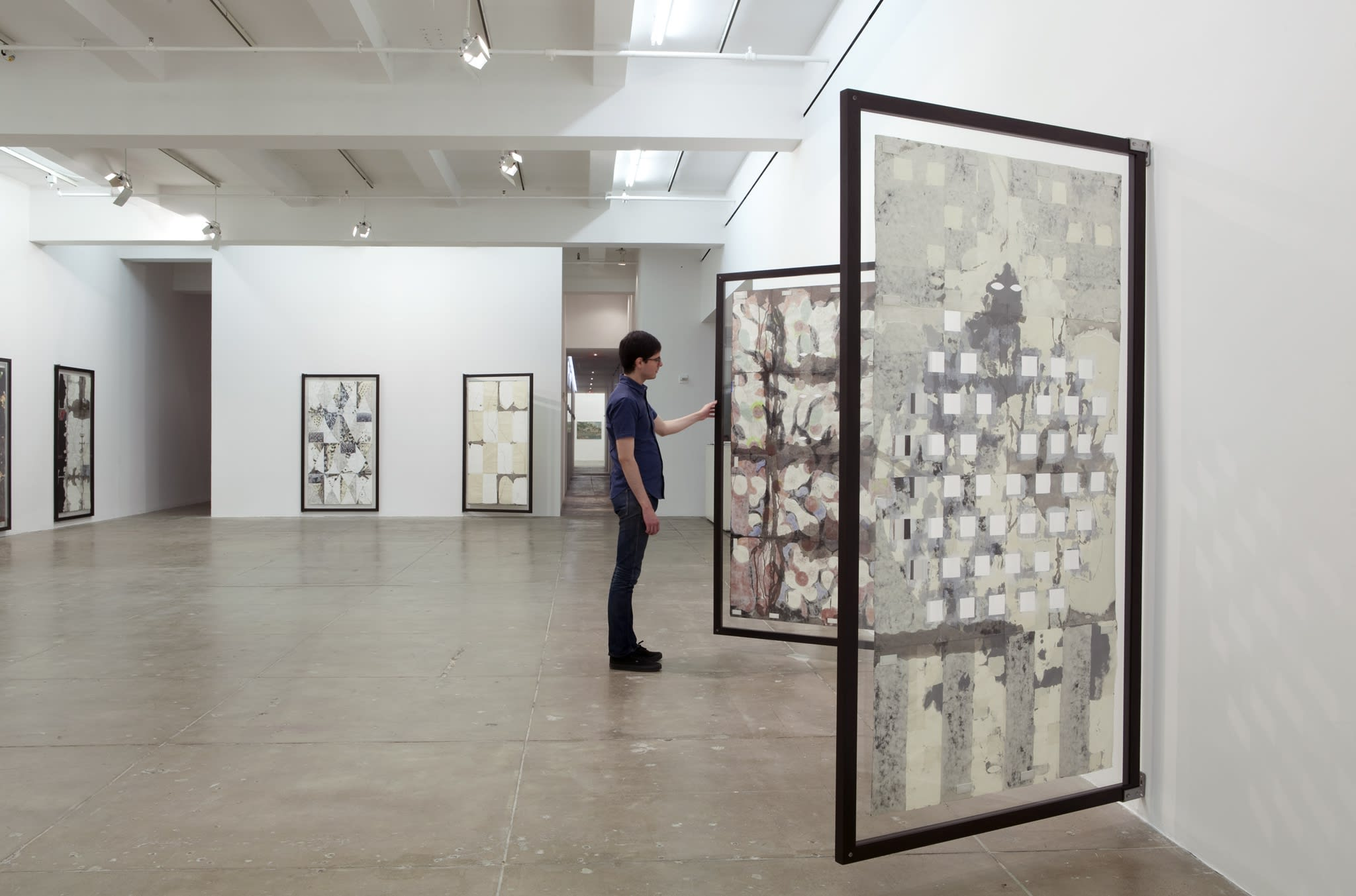 A man views the front and back of a large vertical painting installed on a hinge.