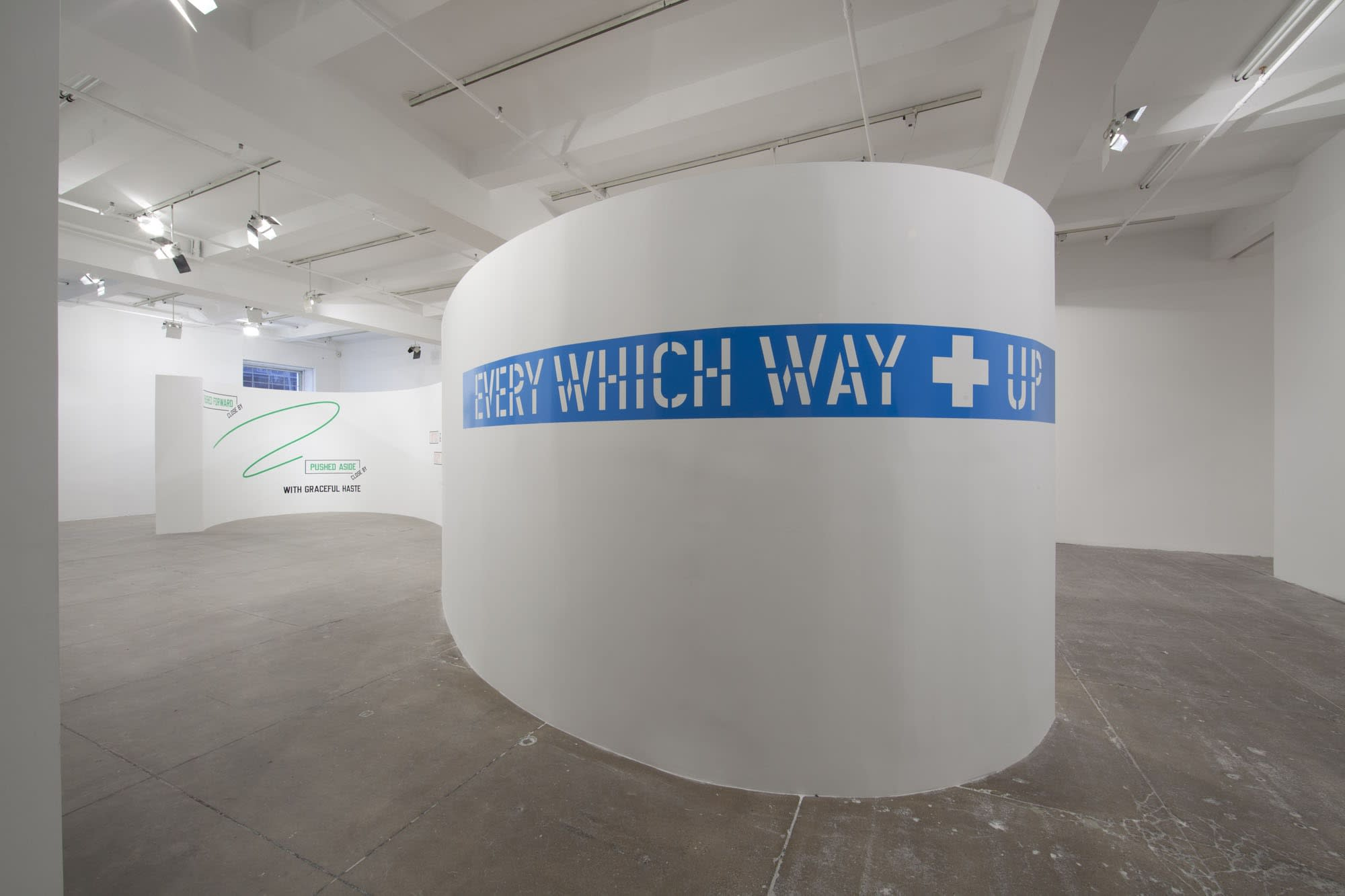 On a curved white wall, large white text over a blue background strip reads: EVERY WHICH WAY UP