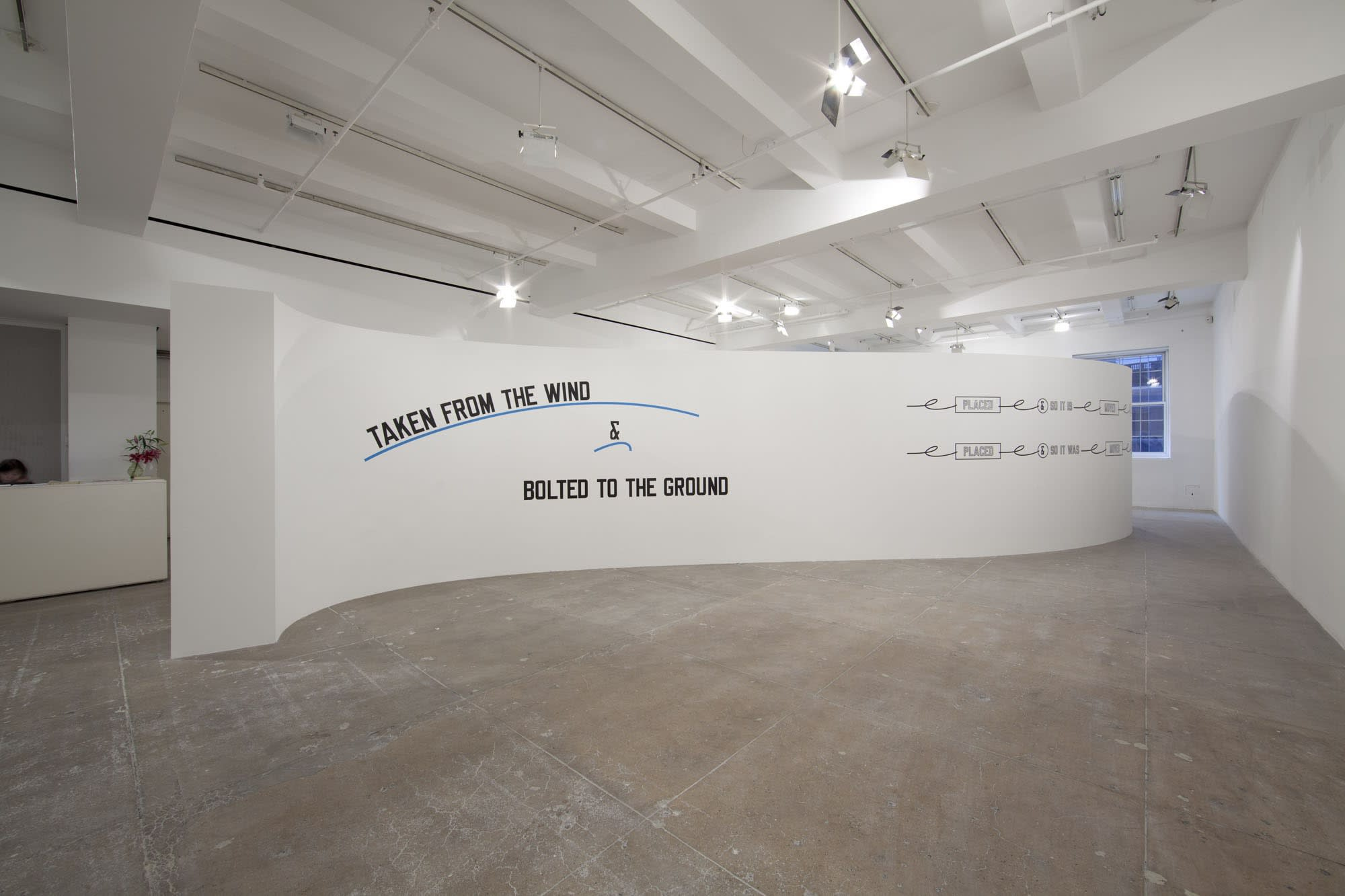 On a curved white wall, large, stylized text reads: TAKEN FROM THE WIND & BOLTED TO THE GROUND.