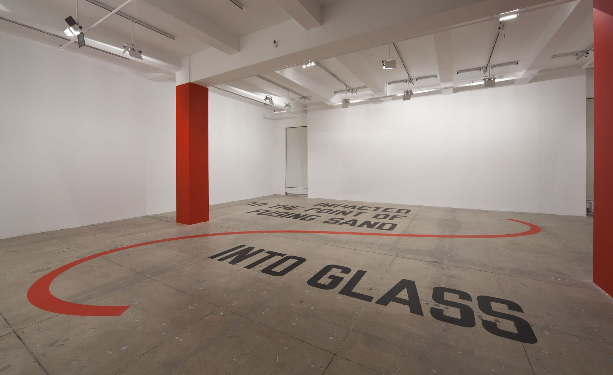 In a large white space with a beige floor and two red columns, large black texts, with a red swoosh design running through it, reads: IMPACTED TO THE POINT OF FUSING SAND INTO GLASS.