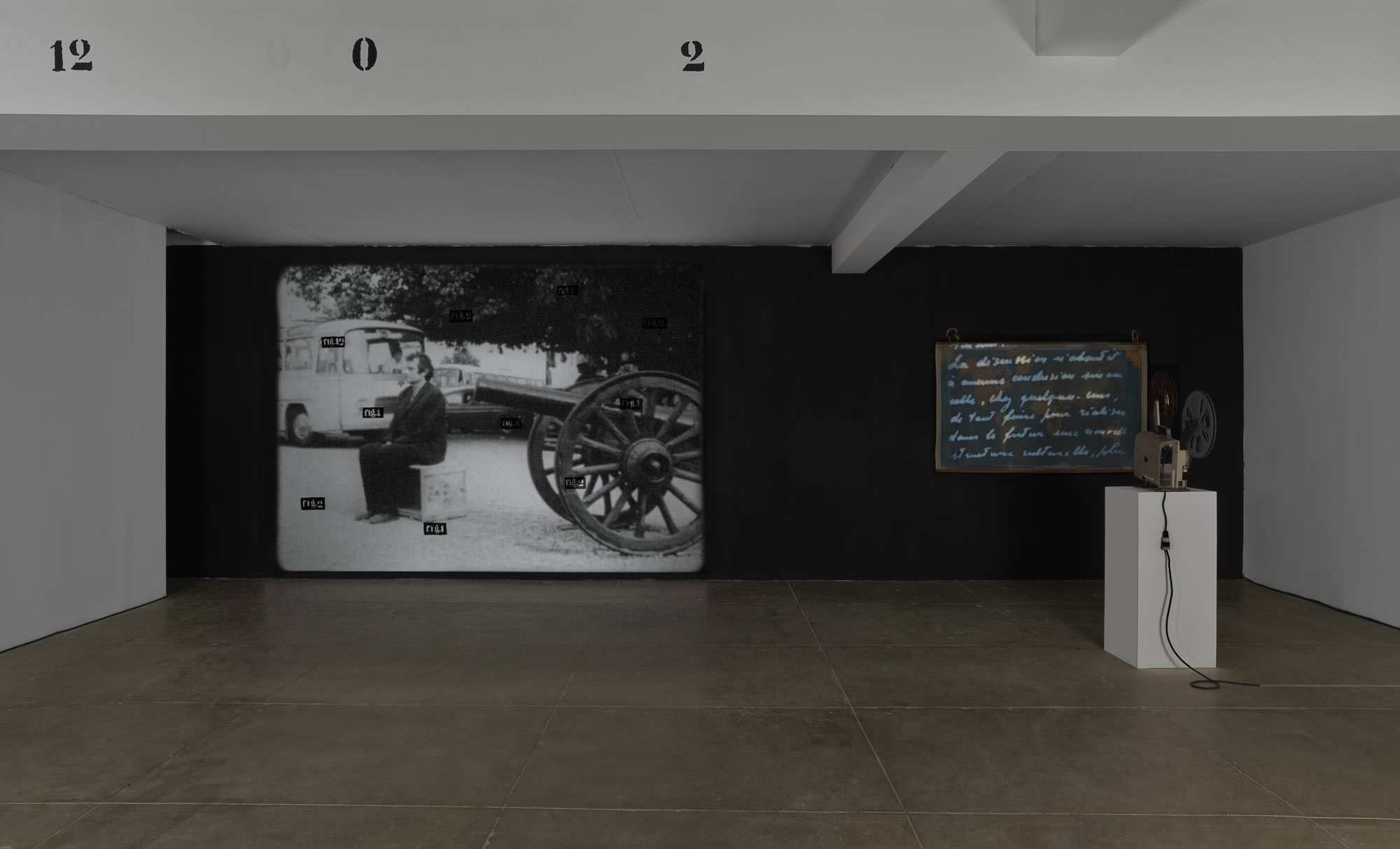 In a dark room, two projections run: one shows french cursive text, the other shows a man sitting in front of a cannon, which points directly at his head. On a beam on the ceiling of the room, texts reads: 12 0 2