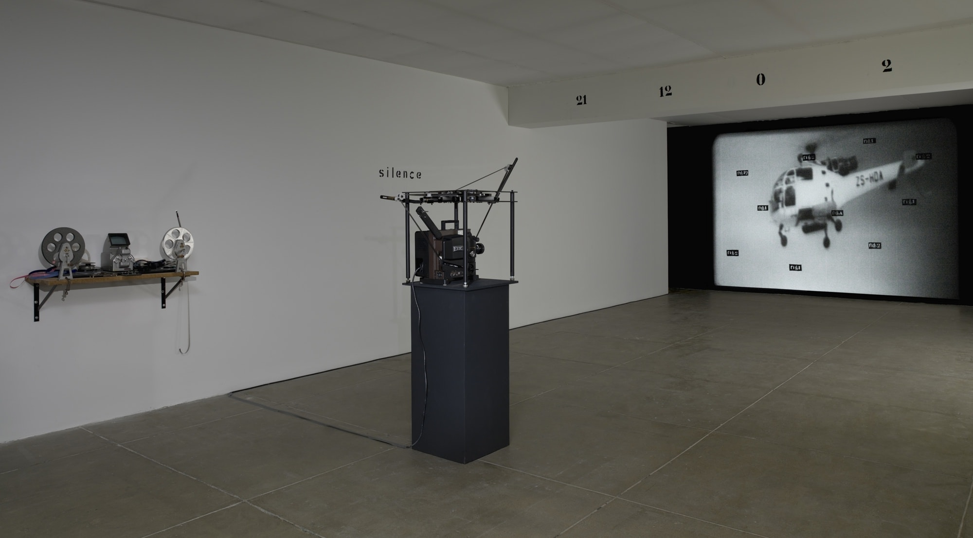 In a white room with a beige floor, a projector runs, showing a large image of a helicopter with small scattered text over it. A beam on the ceiling of the room reads: 21 12 0 2. On the left wall, the text reads: silence.