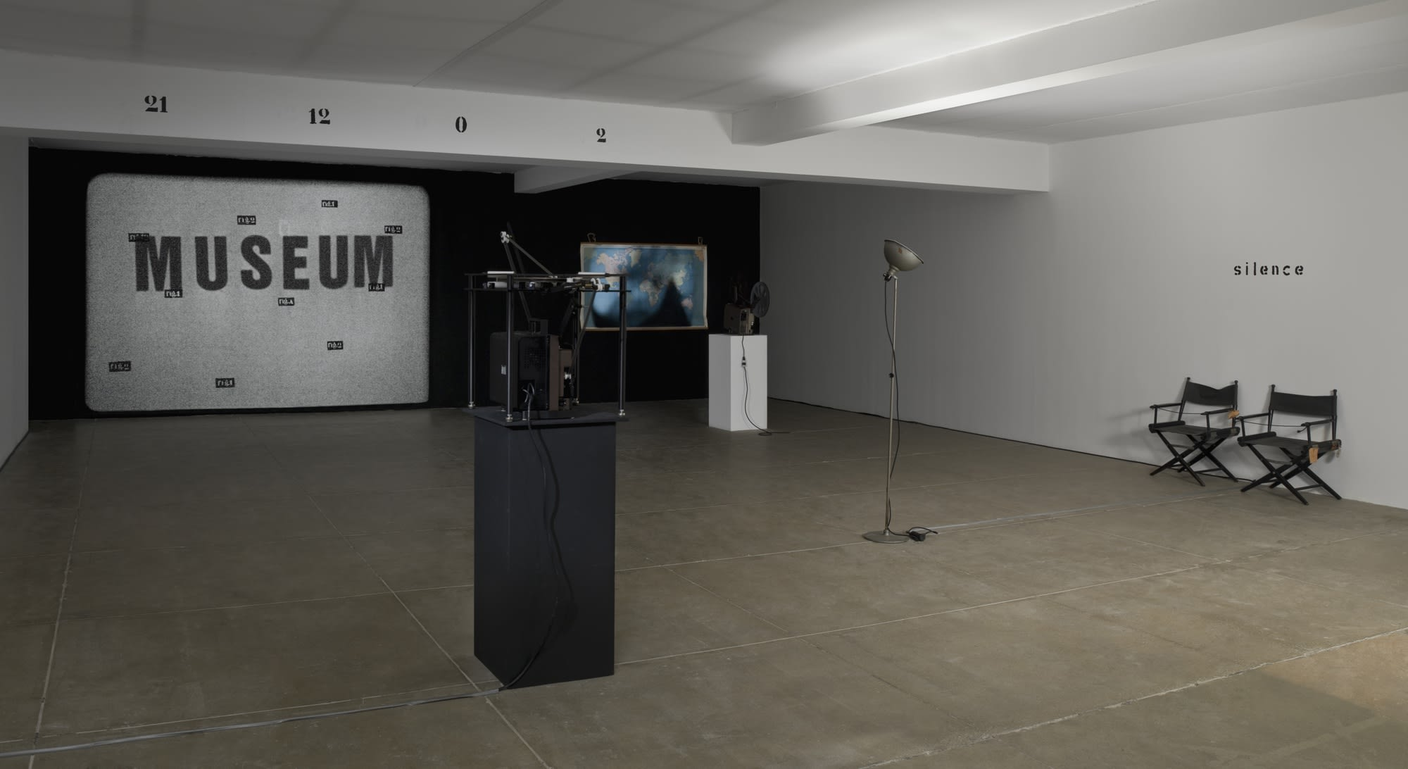 In a white room with a beige floor, two projectors run, showing a world map on one, and a large image of that says MUSEUM with small scattered text over it. A beam on the ceiling of the room reads: 21 12 0 2. On the right wall, text reads: silence.