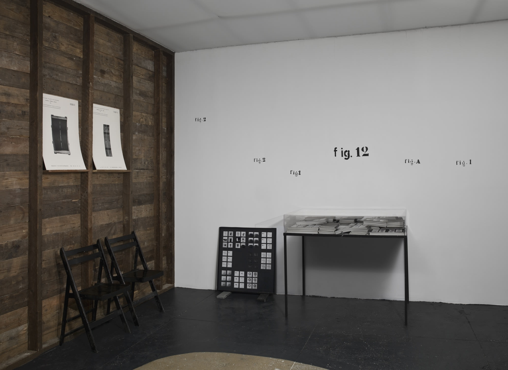 In a room with black floors, a white ceiling, a wooden wall on the left and a white wall straight ahead, there are two chairs by a table. The table is covered in stacks of paper, which is then covered by a glass barrier. Text on the white wall reads: fig.