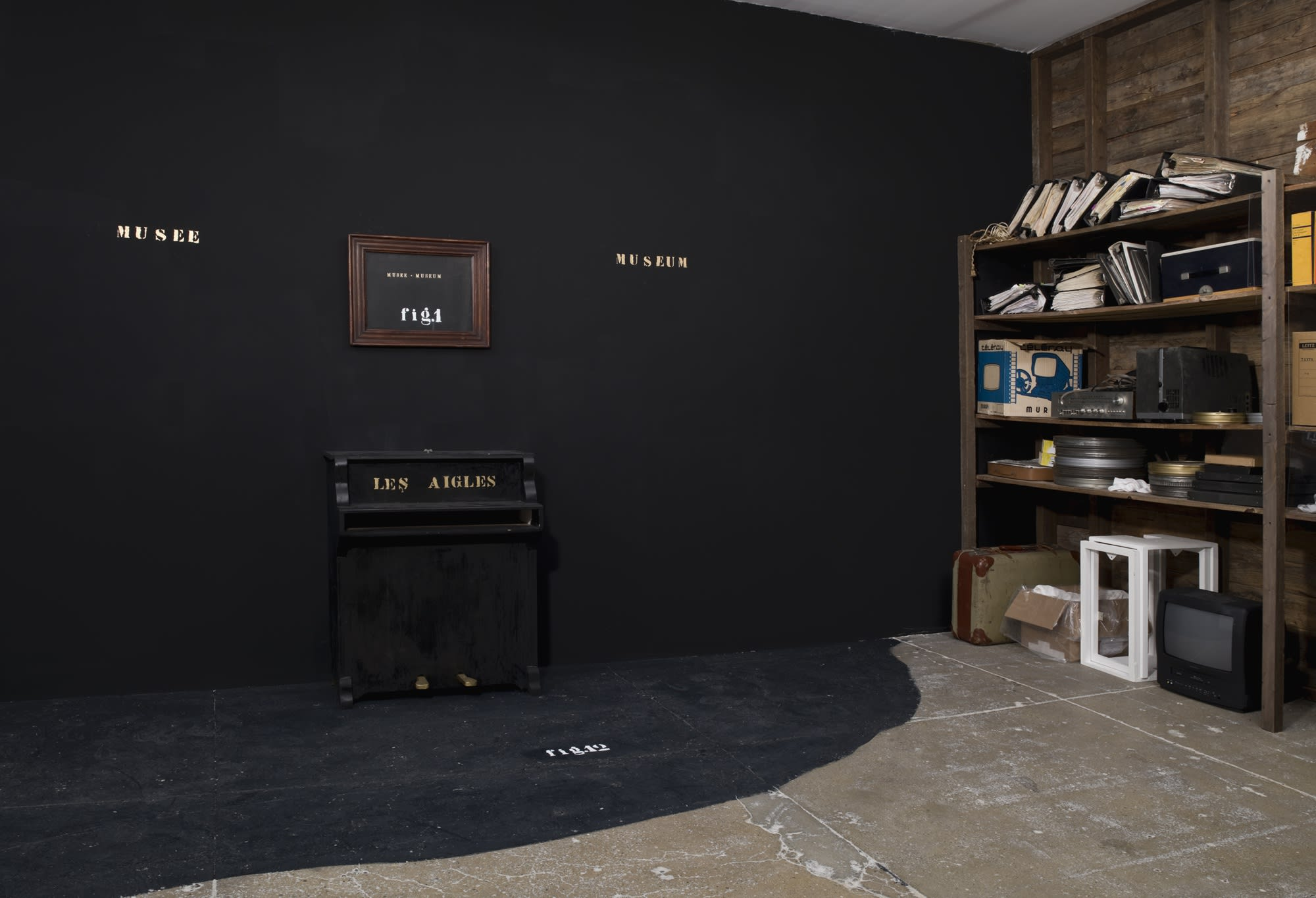 On a black wall, gold text reads MUSEE and MUSEUM on either side of a wood frame containing a black painting that reads the same thing, along with: fig. 1, in white text. Under it, gold text on a black baby piano reads: DES AIGLES. On the right wall, a wo