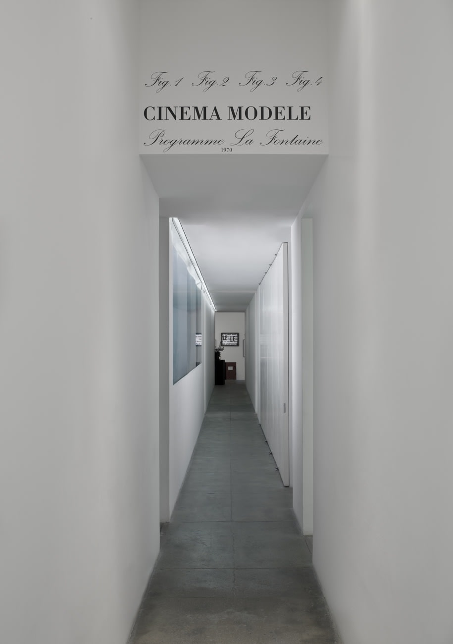 A sign on the ceiling at the start of a long hallway into the exhibition reads, in black cursive: Fig. 1 Fig. 2 Fig. 3 Fig. 4 CINEMA MODELE Programme La Fontaine 1970