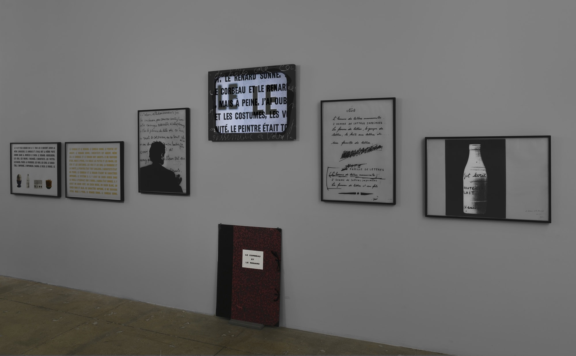 On a white wall, various framed works of drawing and text hang, including a projection of the words: LE LE.