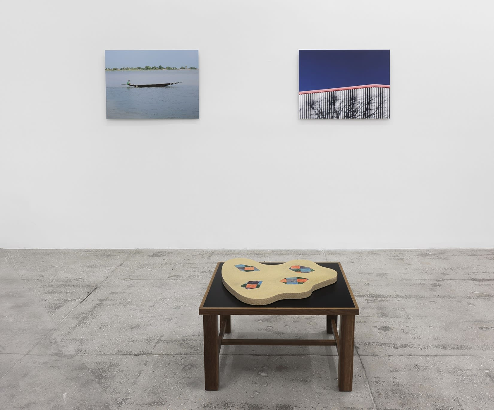 2 photographs hang on a white wall; on the left, a canoe in water and on the right, a roof and sky. A flat sculpture sits on a platform in the foreground.