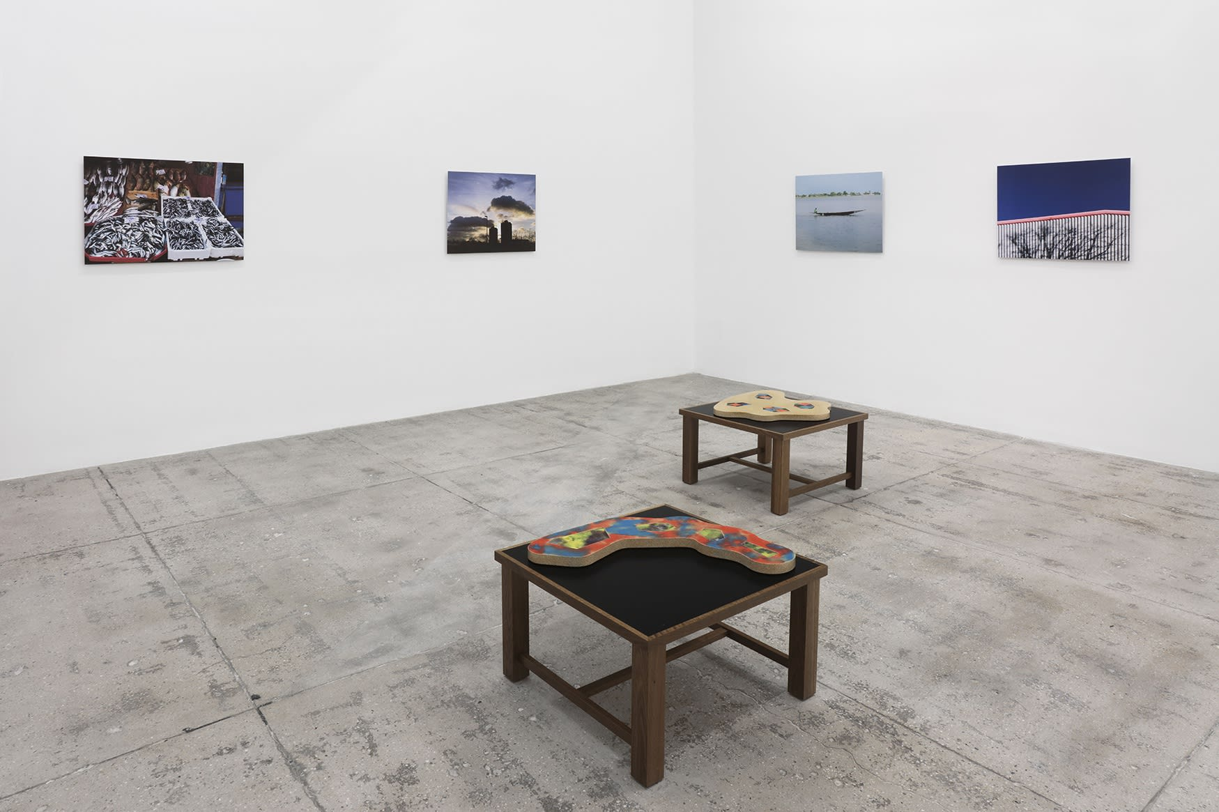 4 photographs hang in the corner of a large white room; 2 flat sculptures sit on wooden platforms in the foreground.