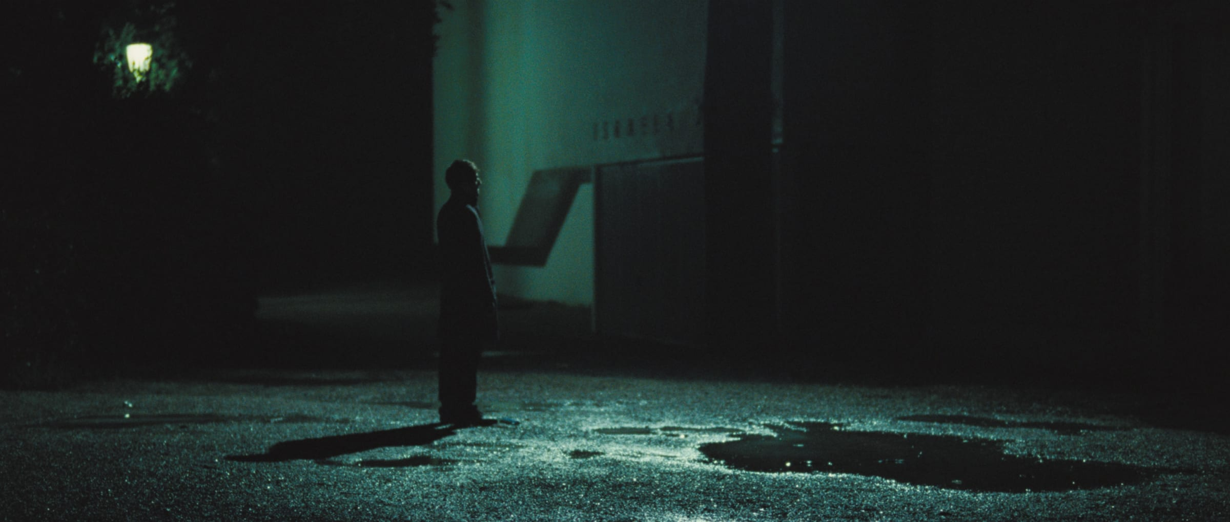 A man stands alone at night in an empty parking lot with a puddle; green light emanates from a street lamp in the background.