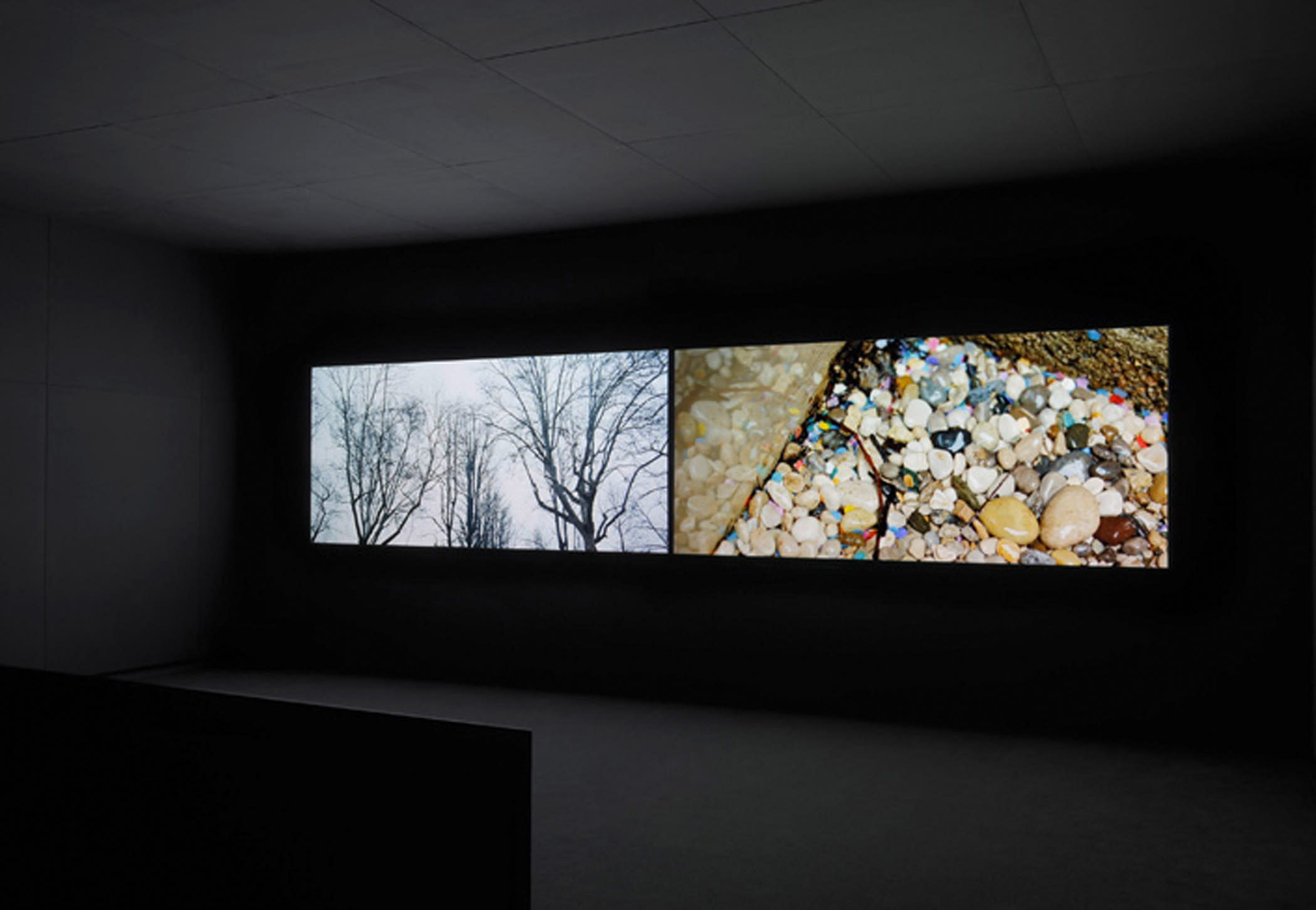 2 projection screens sit horizontally in a dark theater. The left displays trees and an overcast sky; the right colorful stones.