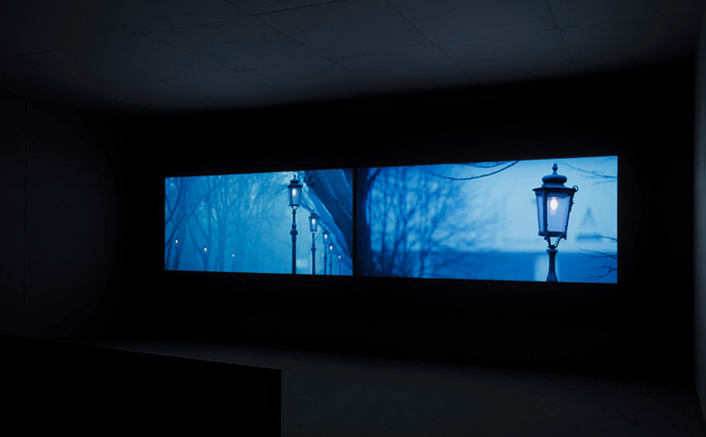 2 projection screens sit horizontally in a dark theater, both display street lamps in front of an aqua sky.