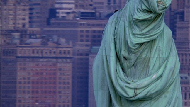 The statue of liberty is cropped at the bust from the posterior view. High-rise buildings fill the background.
