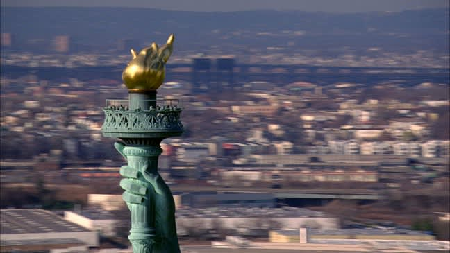The statue of liberty's torch appears on the left side of the image, with out of focus buildings in the background.