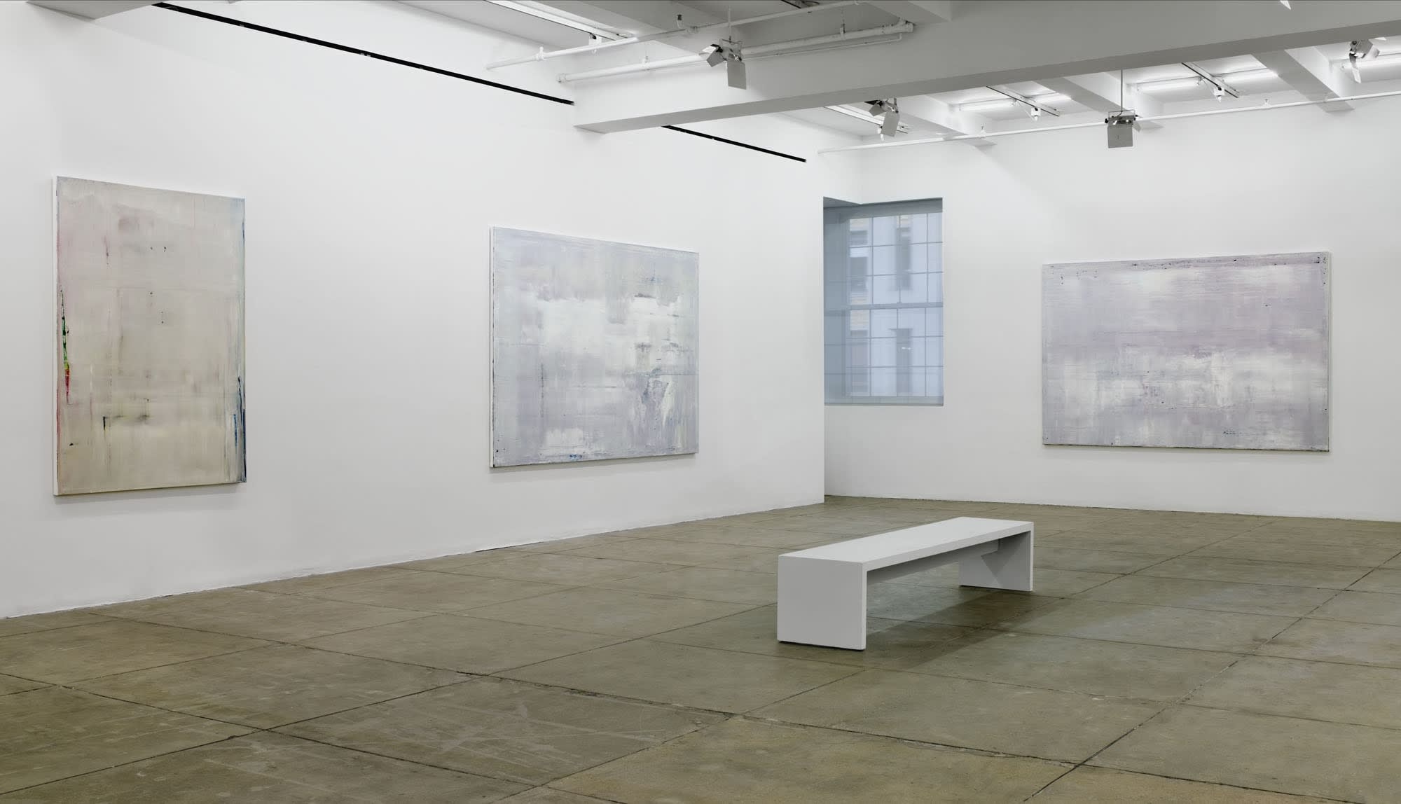 3 large, light grey, abstract paintings hang in the corner of a room. There is a window in the corner and a white bench in the center of the floor.