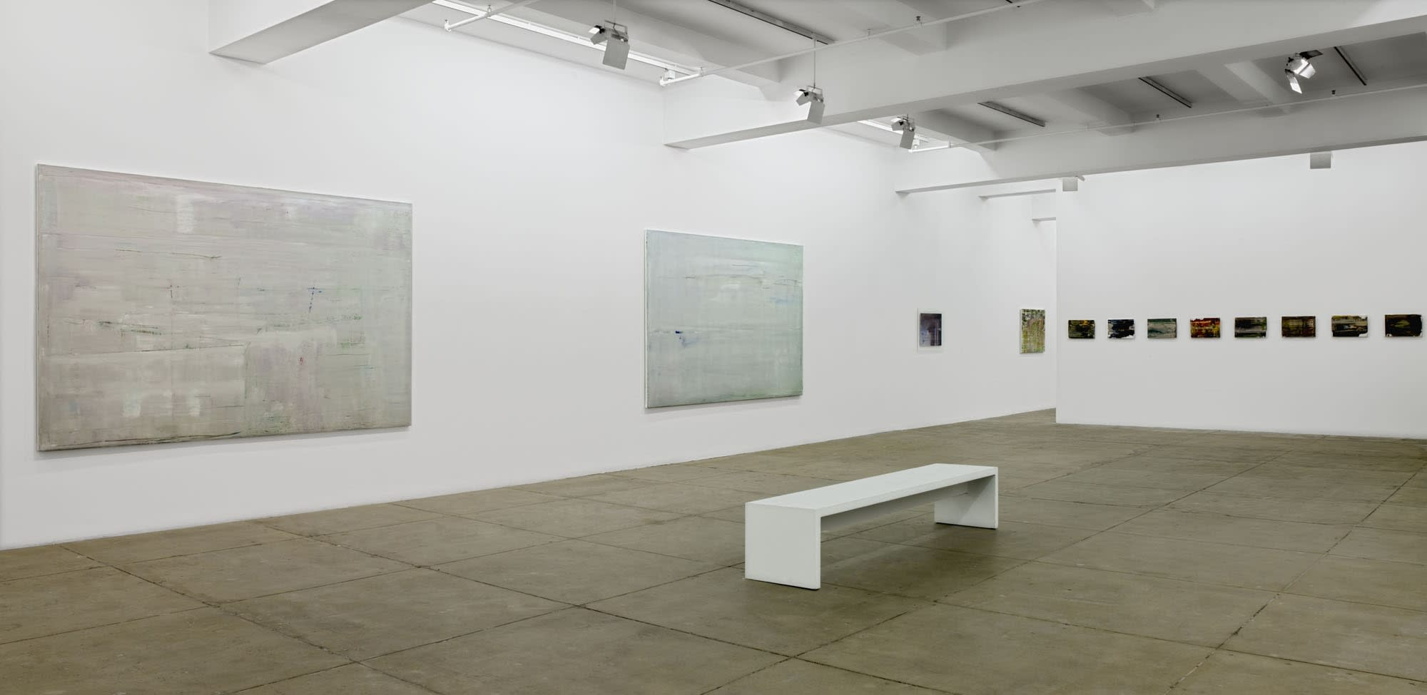 On the left, two large, gray abstract paintings hang on the wall. On the right is a row of 10 small, dark, abstract paintings. A white bench sits in the center of the room.