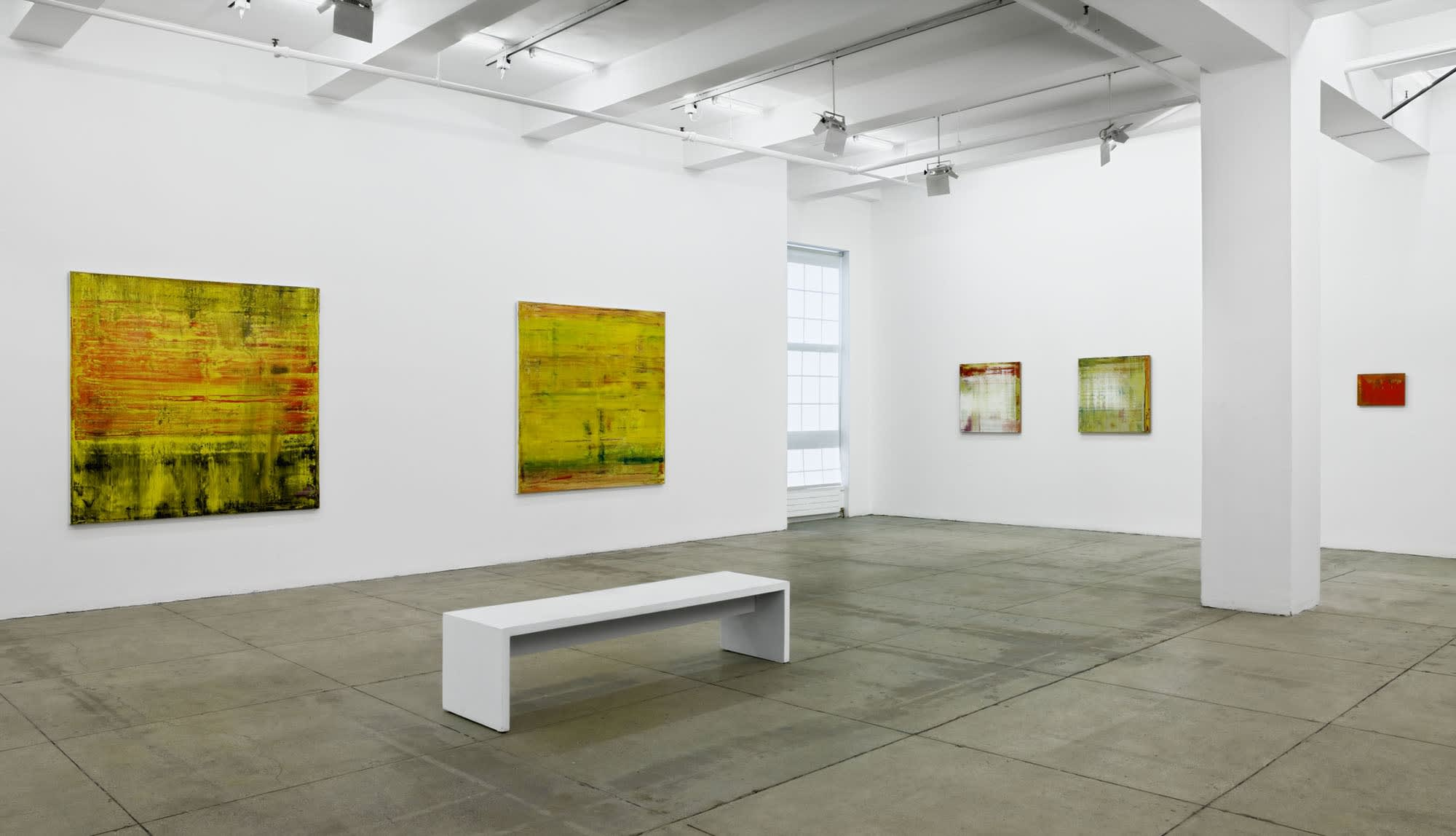5 abstract paintings of various sizes span two walls with a window in-between. A column and a white bench sit in the center of the room.