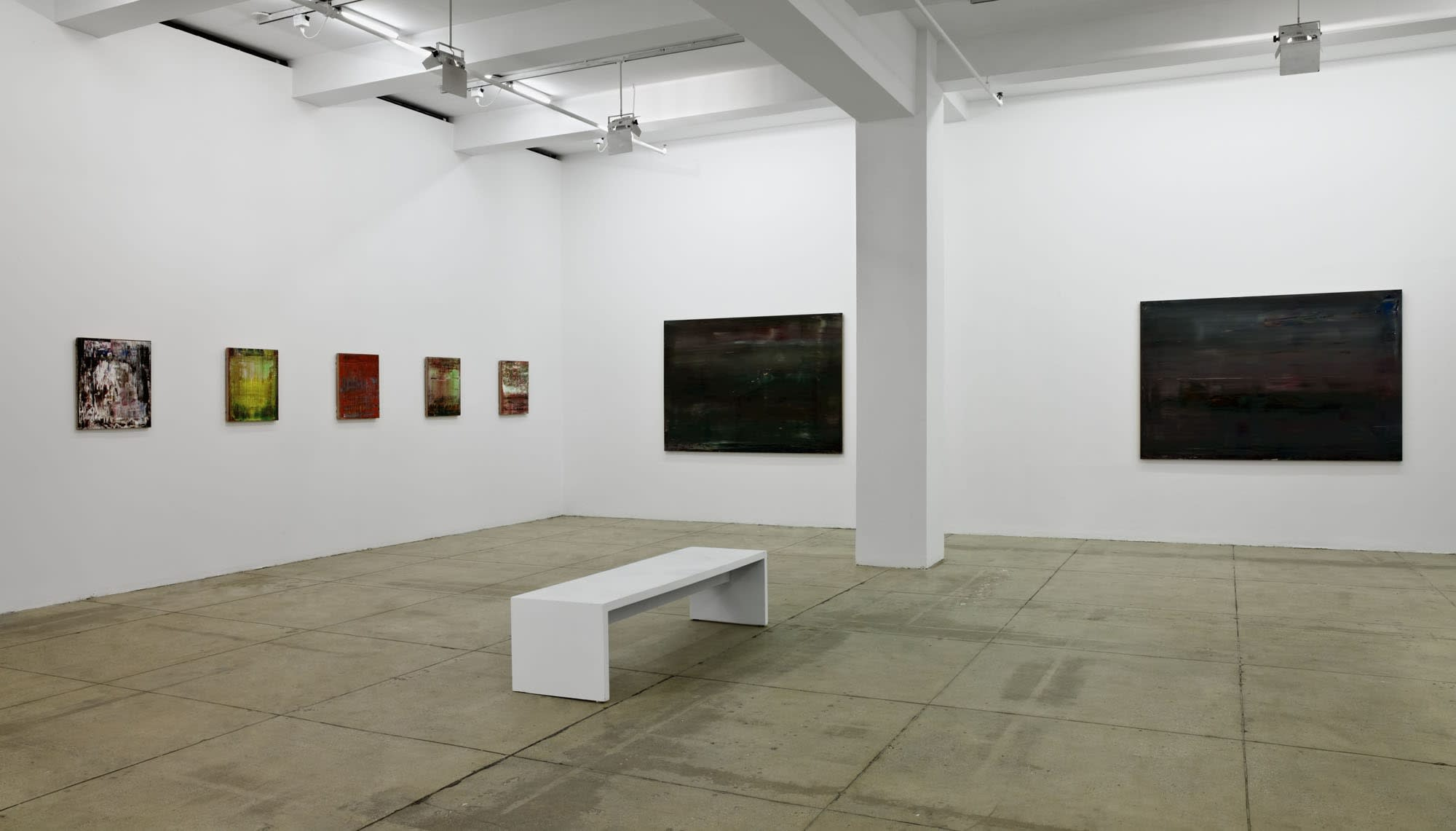 On the left wall are 5 small, colorful, abstract paintings in a row. On the right wall are two large, black abstract paintings. A white column and bench sit in the center of the room.