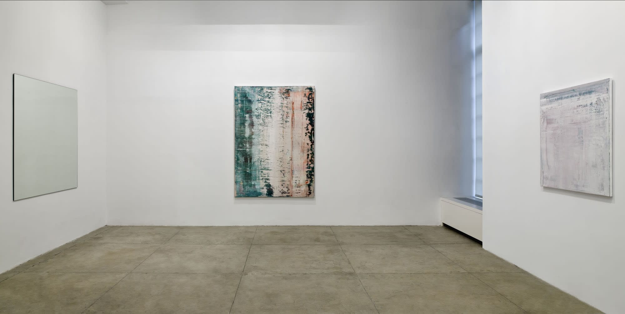 3 abstract paintings hang on 3 walls forming a corner. There is a window on the right.