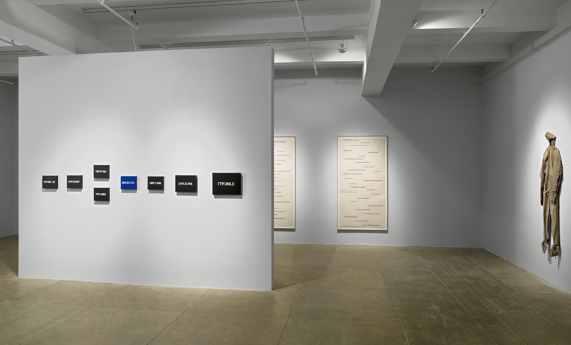 A floating wall displays 8 works with backwards text. Behind the wall are two large framed works with text on paper, and to the right hangs a beige full-body suit.