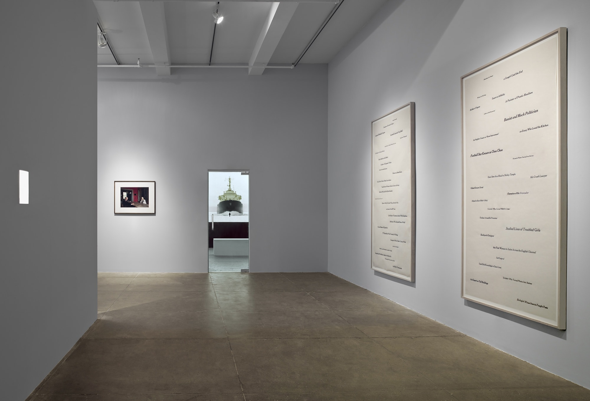 On the left wall there is a square of light. In the center is a model ship visible through a doorway, next to a framed photograph.  On the right wall hang two framed works with text on paper.