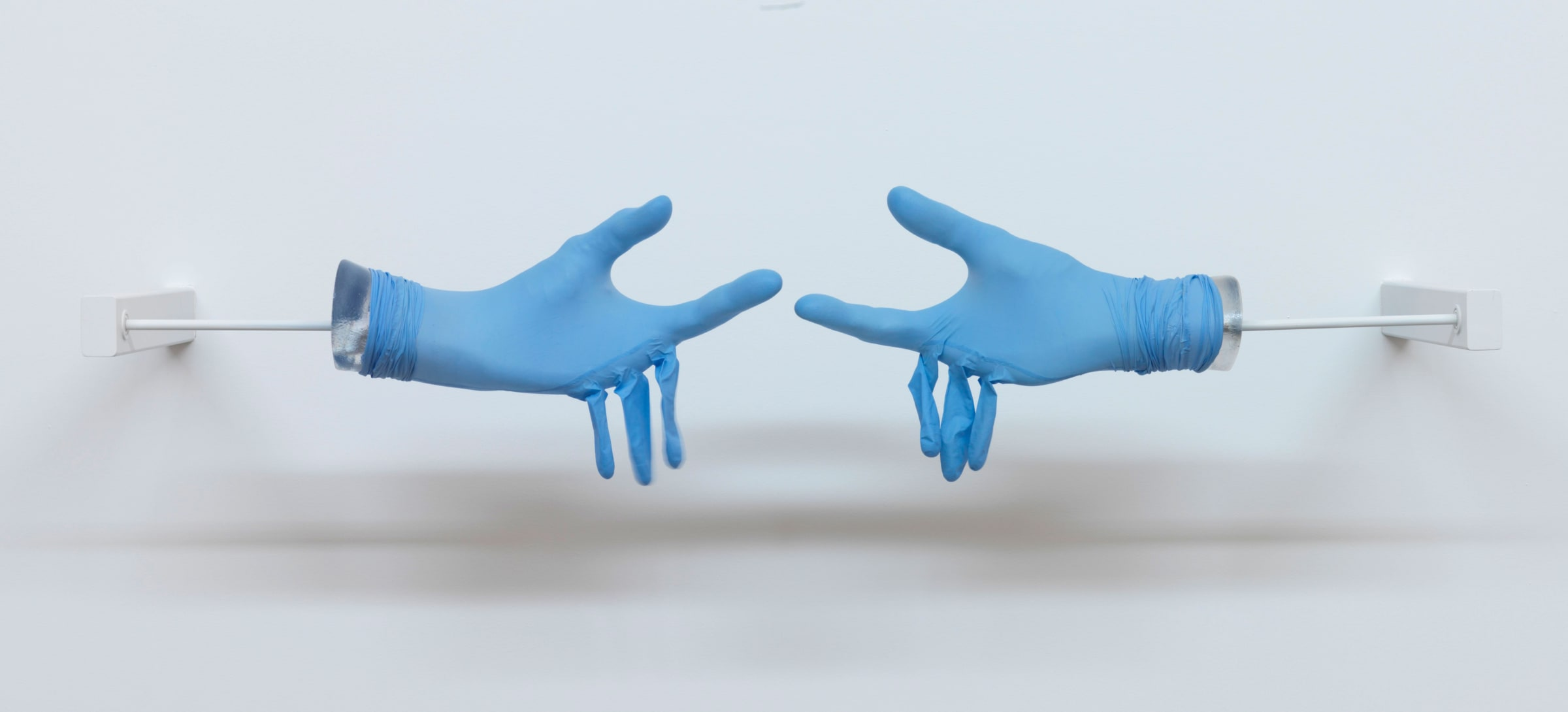 Two blue medical gloves are stretched over plaster hands reaching for each other. The middle, ring and pinky finger are empty and hang limply.