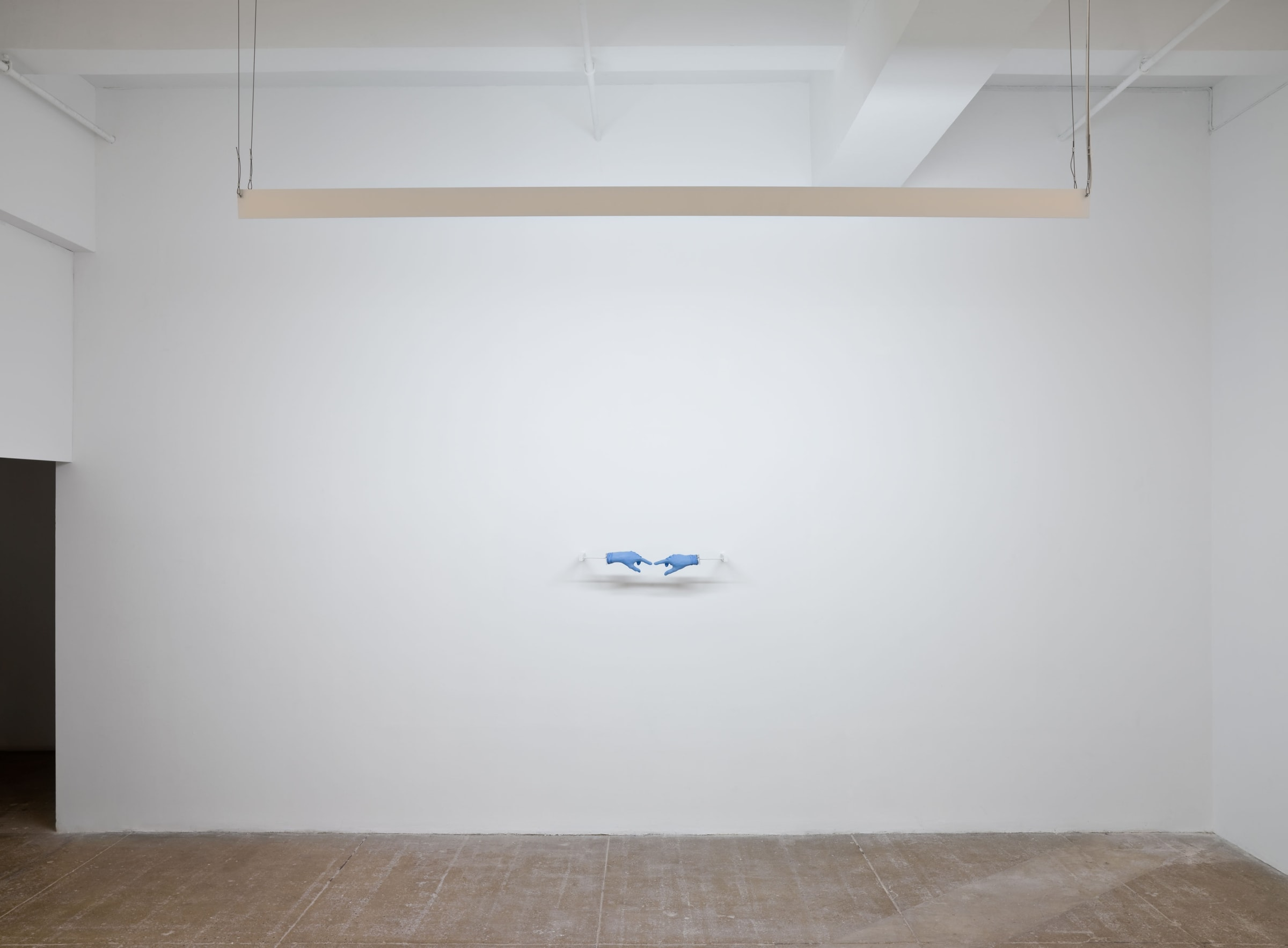 Two blue medical gloves stretched over plaster hands are seen pointing towards each other from a distance in front of a white wall. A fluorescent lamp hangs above them.