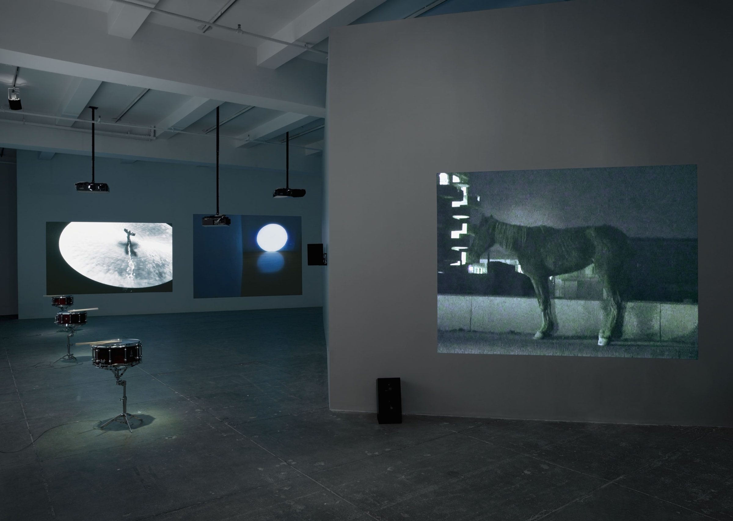 3 projections fill a darkened room while 3 snare kits sit in a line on the left. The projections display a cymbal, a circle of light, and a horse.