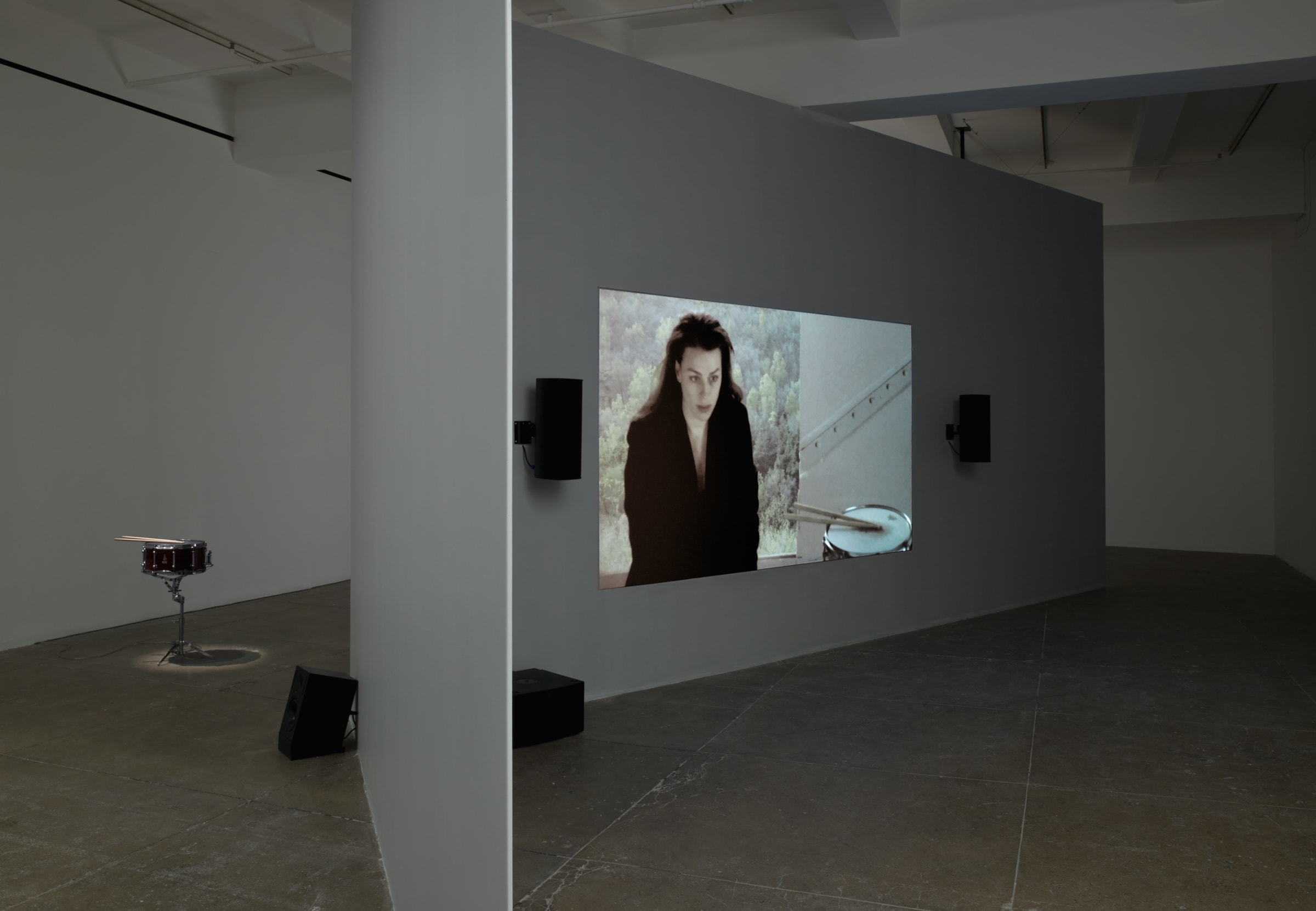 A projection of a woman is centered on a floating wall; 4 black speakers are visible around the screen and a snare kit sits behind the wall.