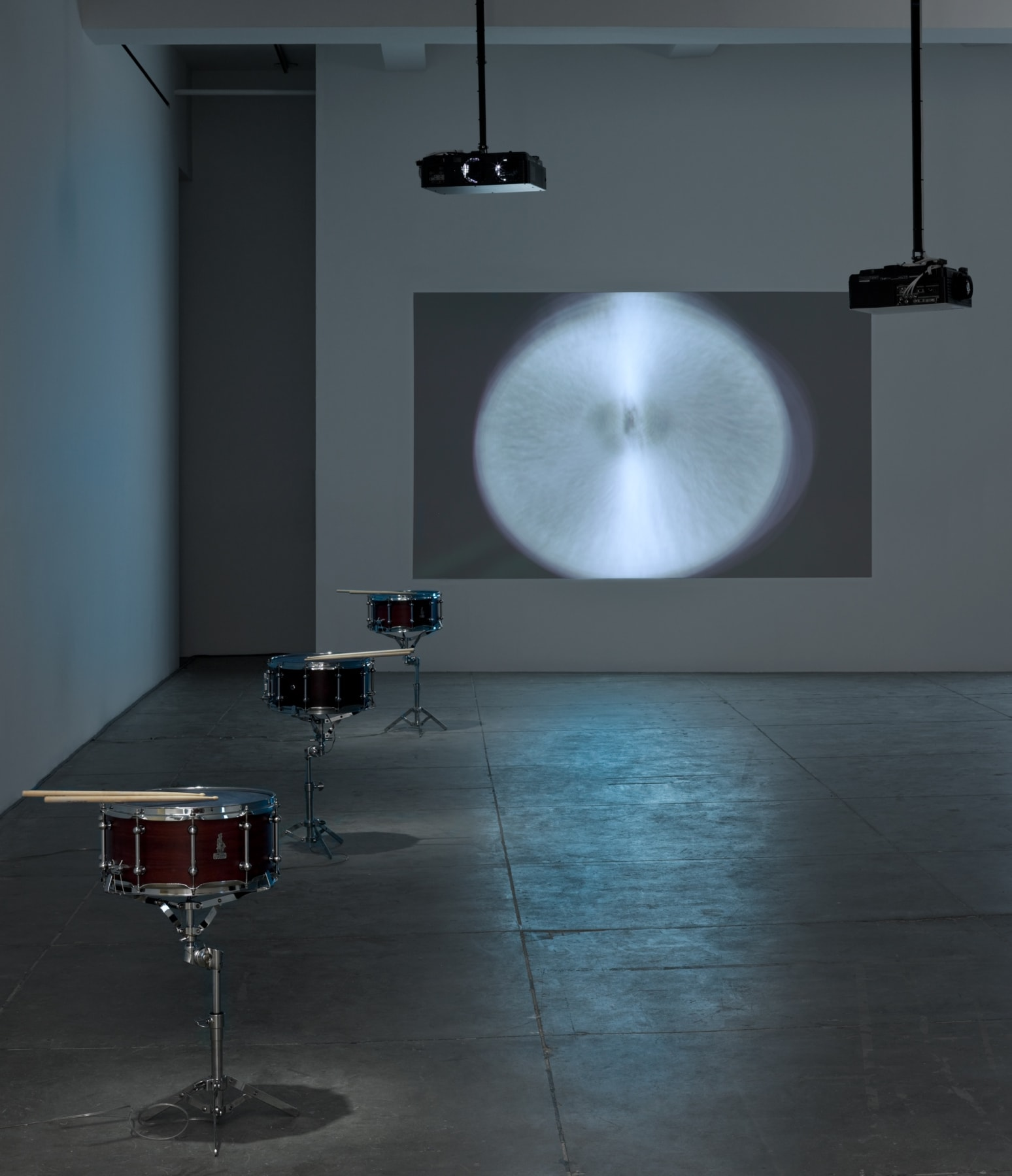 A cymbal with a motion blur is projected onto a wall. 2 black projectors are suspended from the ceiling. 3 snare kits sit in a line on the left side of the room.
