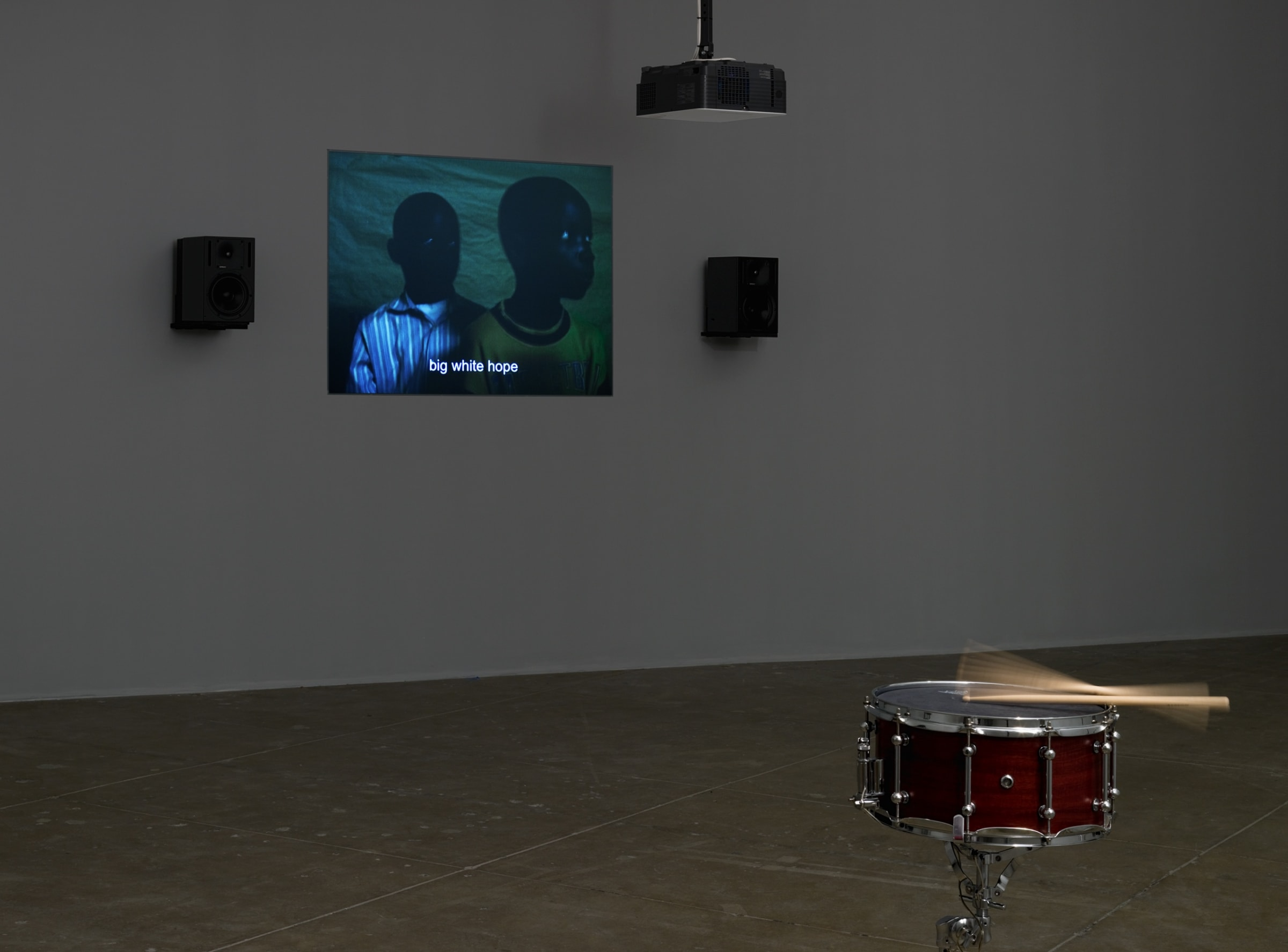 A snare-kit with moving drum sticks stands in front of a projection of two young black boys with the subtitle, big white hope.
